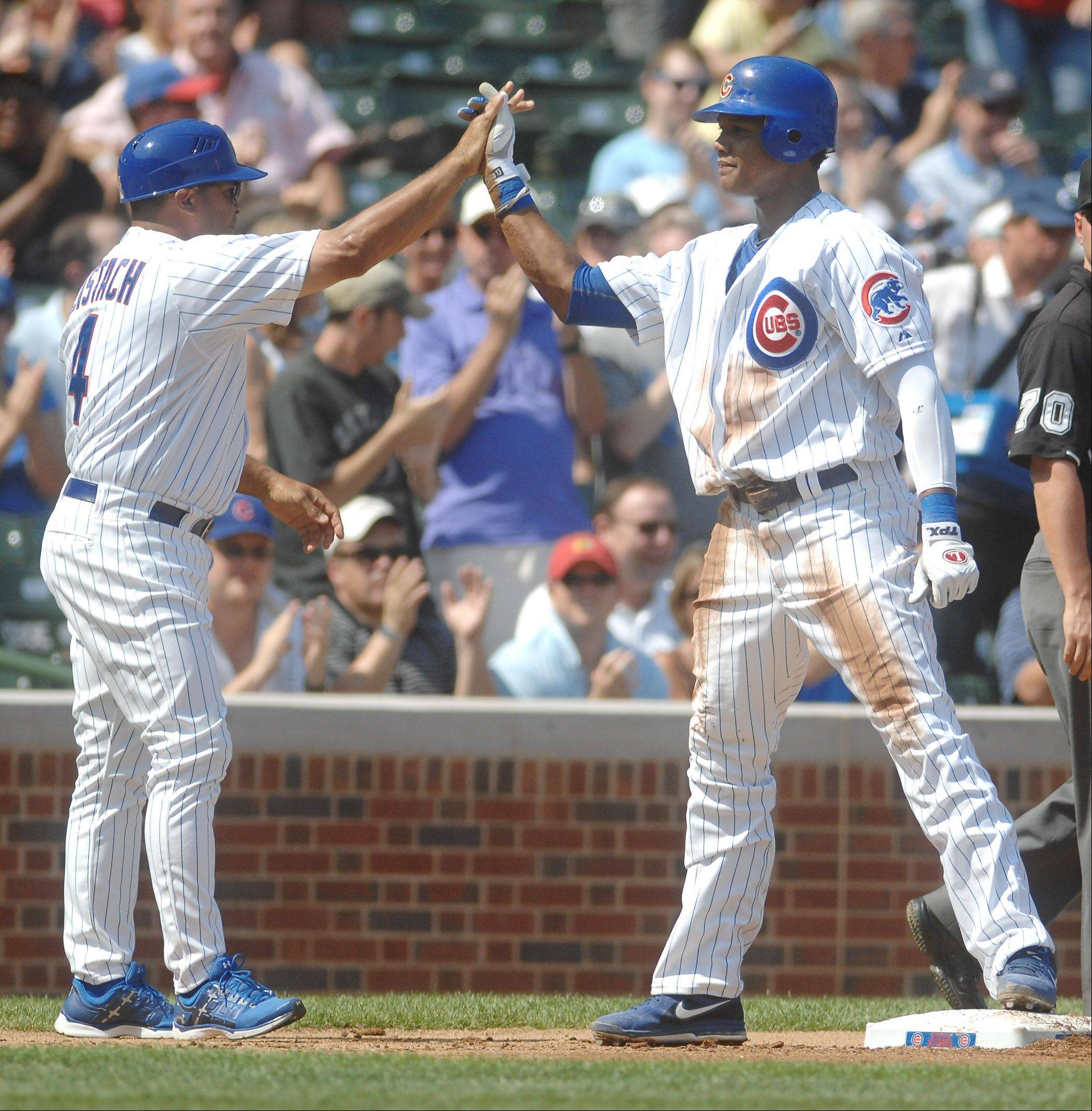 Chicago Cubs shortstop Starlin Castro is congratulated by third base coach Pat Listach after a first-inning RBI triple.