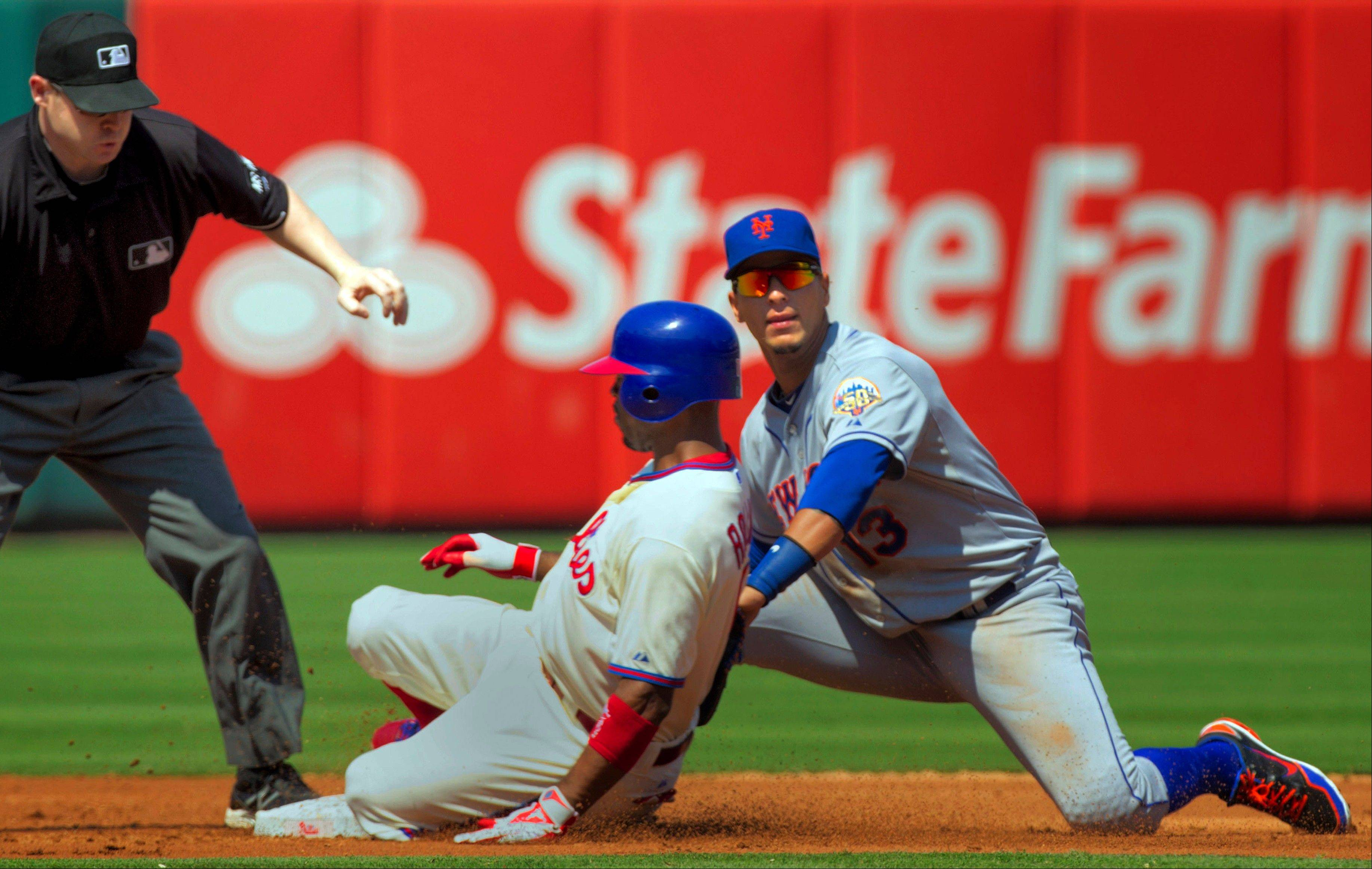 The Phillies' Jimmy Rollins safely slides into second for a double past New York Mets shortstop Ronny Cedeno during the third inning Thursday in Philadelphia. Rollins was benched later in the game.