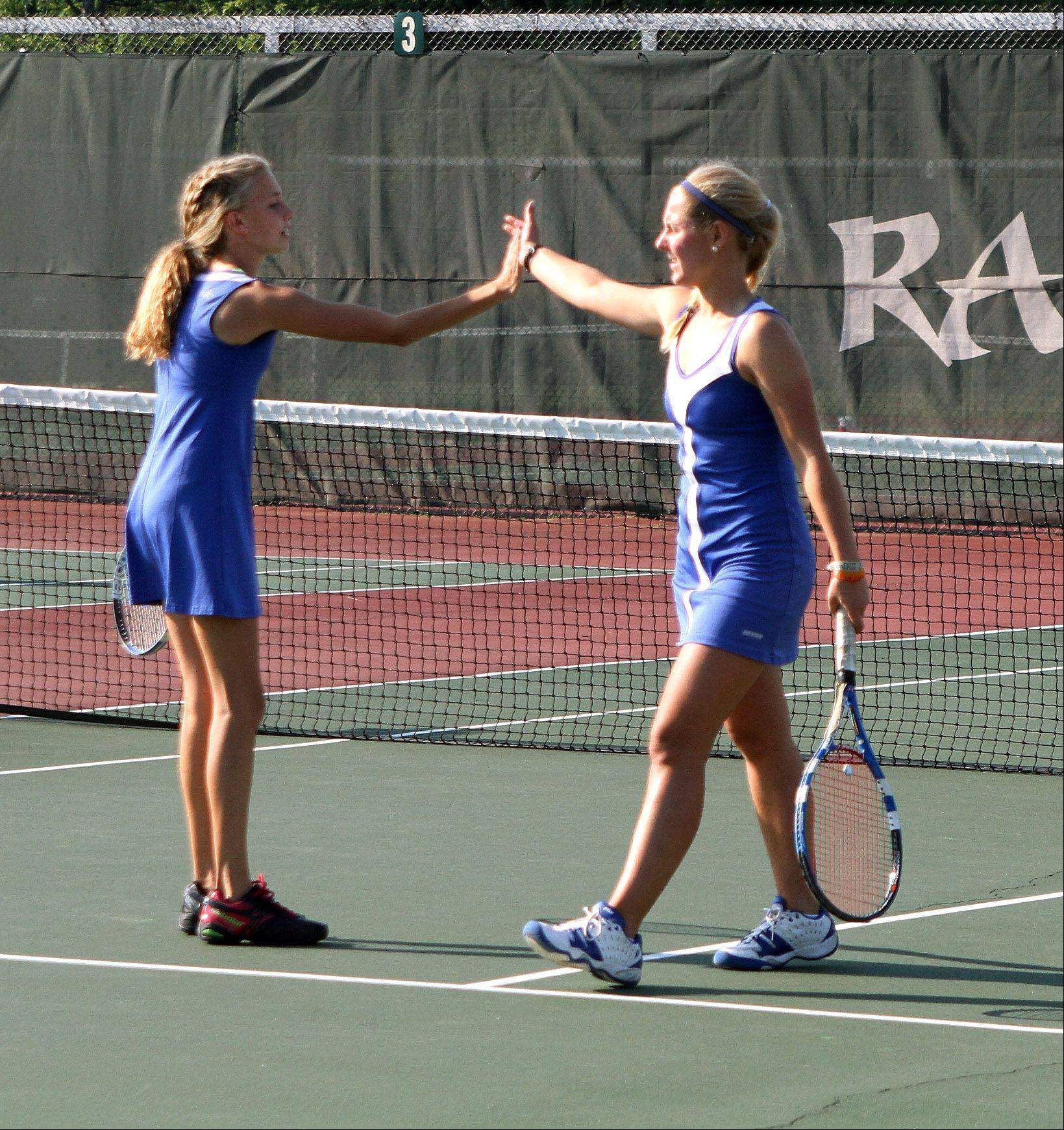 Liz Oprins, right, gives a high-five to her Glenbard South doubles partner Rachel Rettger during their match against Lake Park in girls tennis action on Monday in Glen Ellyn.