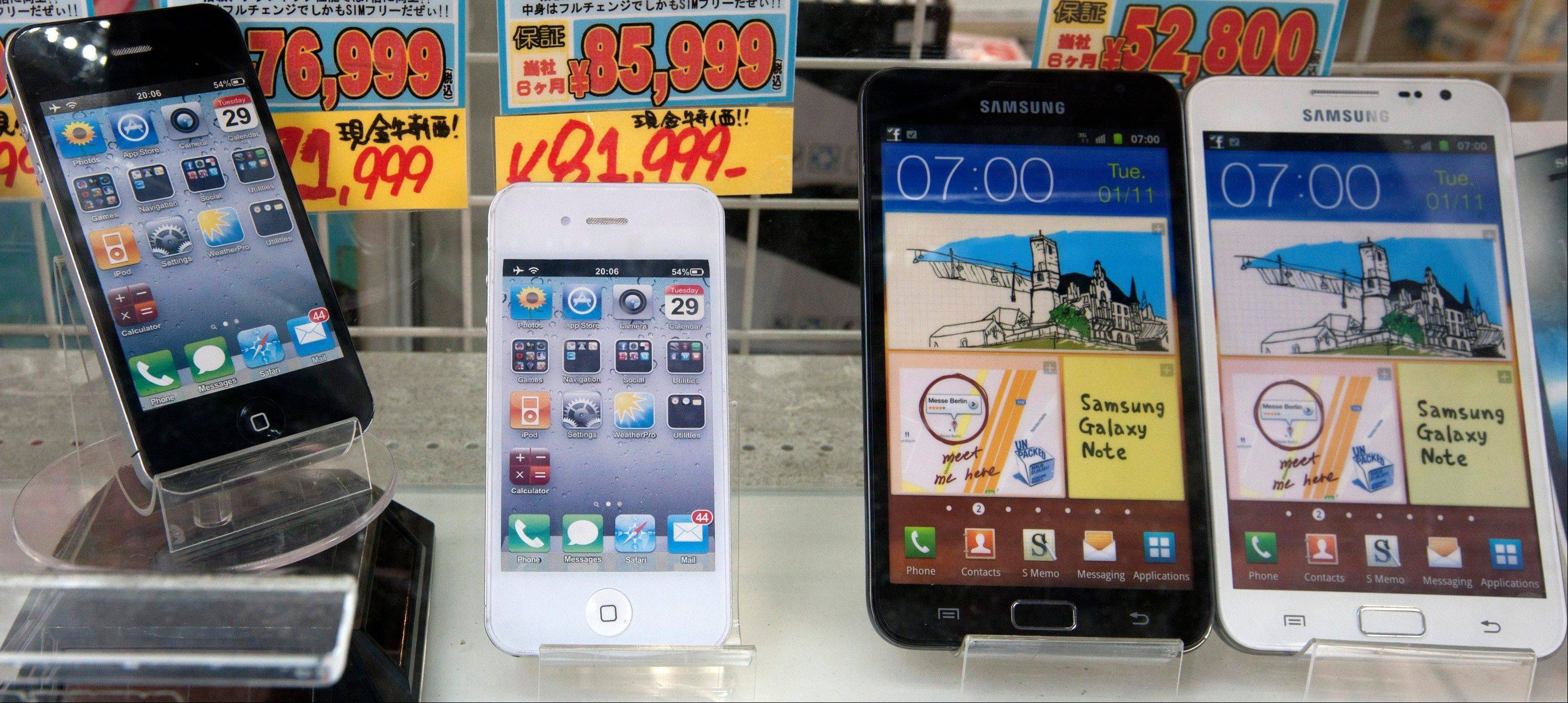 Apple Inc. iPhones, left, and Samsung Electronics Co. Galaxy smartphones are displayed at an electronics store in Tokyo, Japan, on Tuesday, Aug. 28, 2012. Apple Inc. lost a patent lawsuit in Japan as a Tokyo judge ruled that Samsung Electronics Co. smartphones and a tablet computer didn't infringe on an Apple invention for synchronizing music and video data with servers.