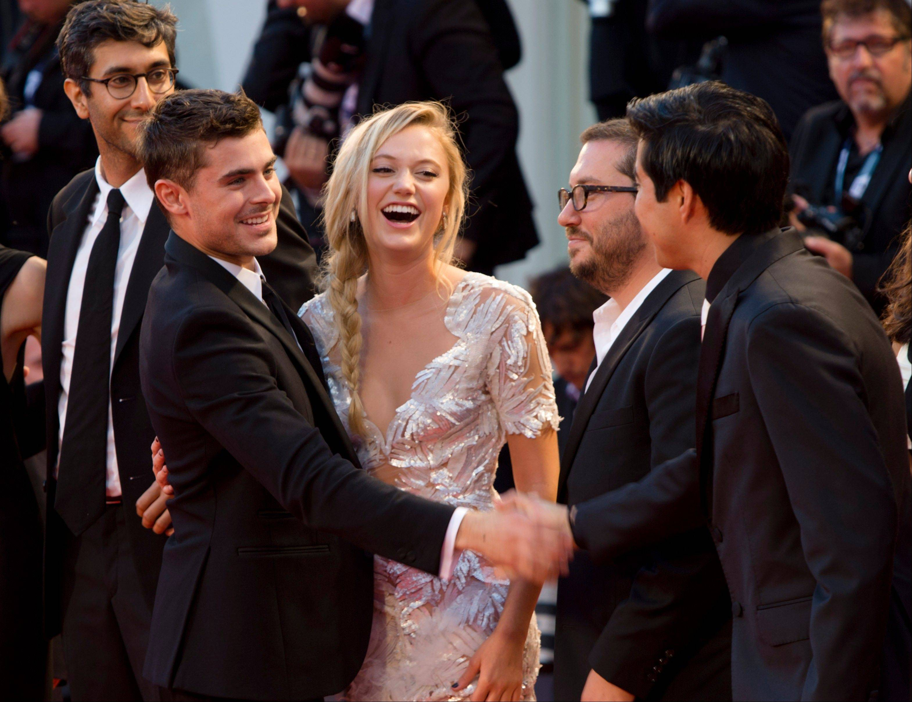 From left, director Ramin Bahrani, actor Zac Efron, actress Maika Monroe, an unidentifird guest, and producer Justin Nappi arrive Friday for the premiere of the movie 'At Any Price' at the 69th edition of the Venice Film Festival in Venice.