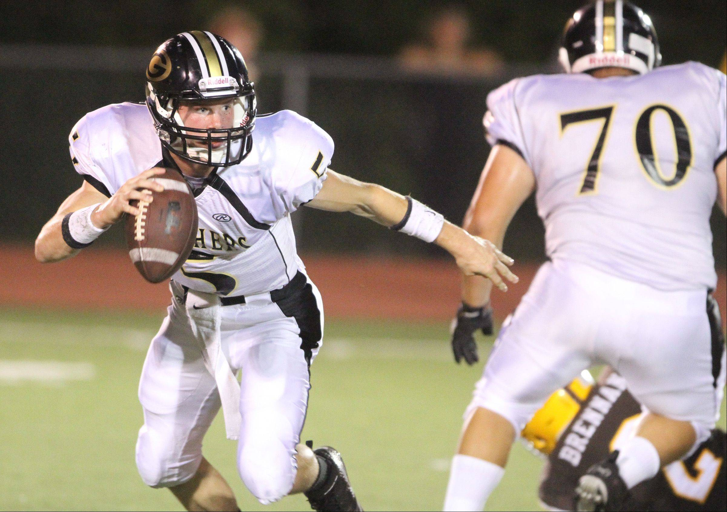 Glenbard North quarterback Brian Murphy scrambles with the ball against Carmel defenders on Friday in Mundelein.