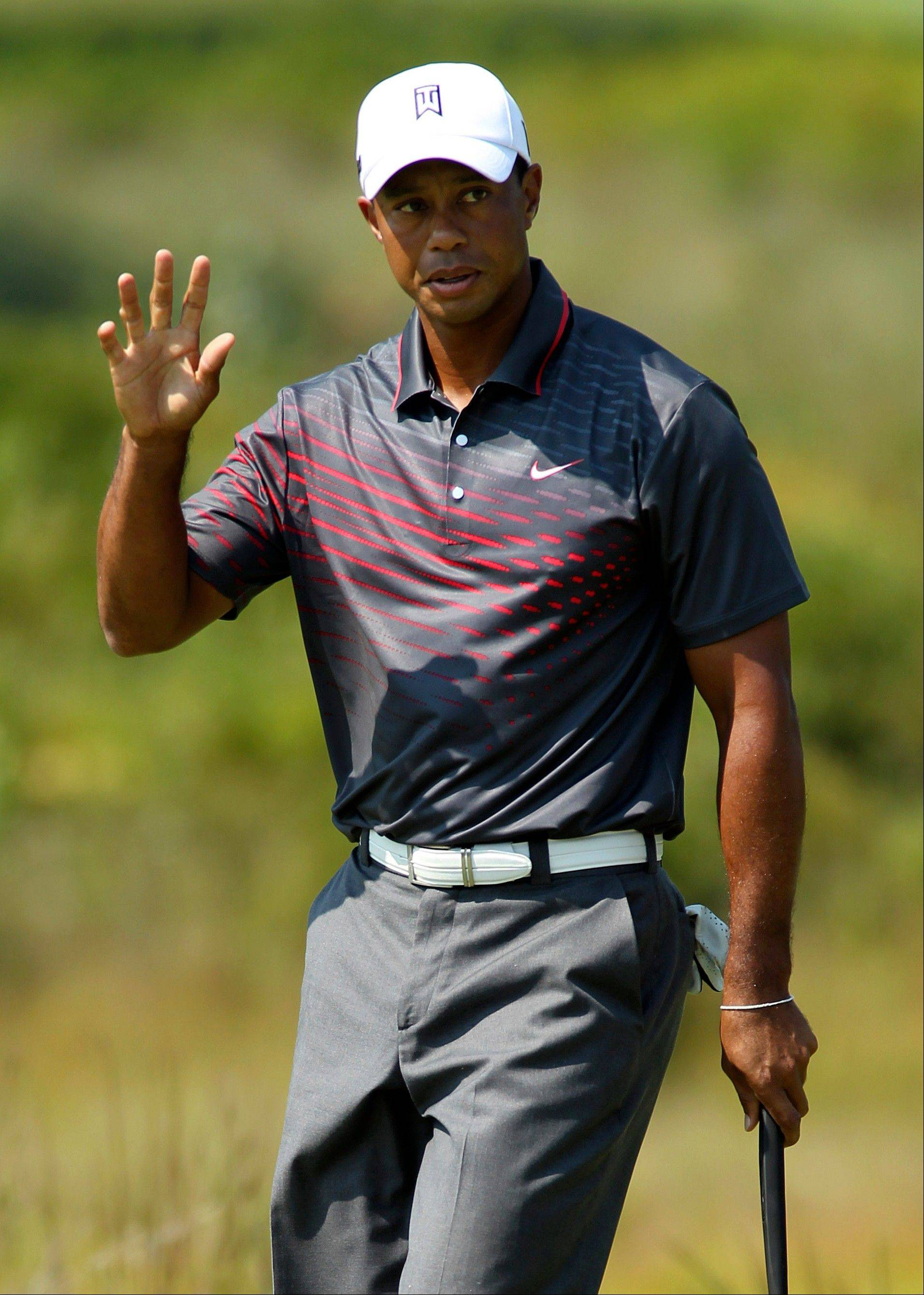 Tiger Woods waves to the crowd Friday after making a birdie putt on the second hole during the first round of the Deutsche Bank Championship.