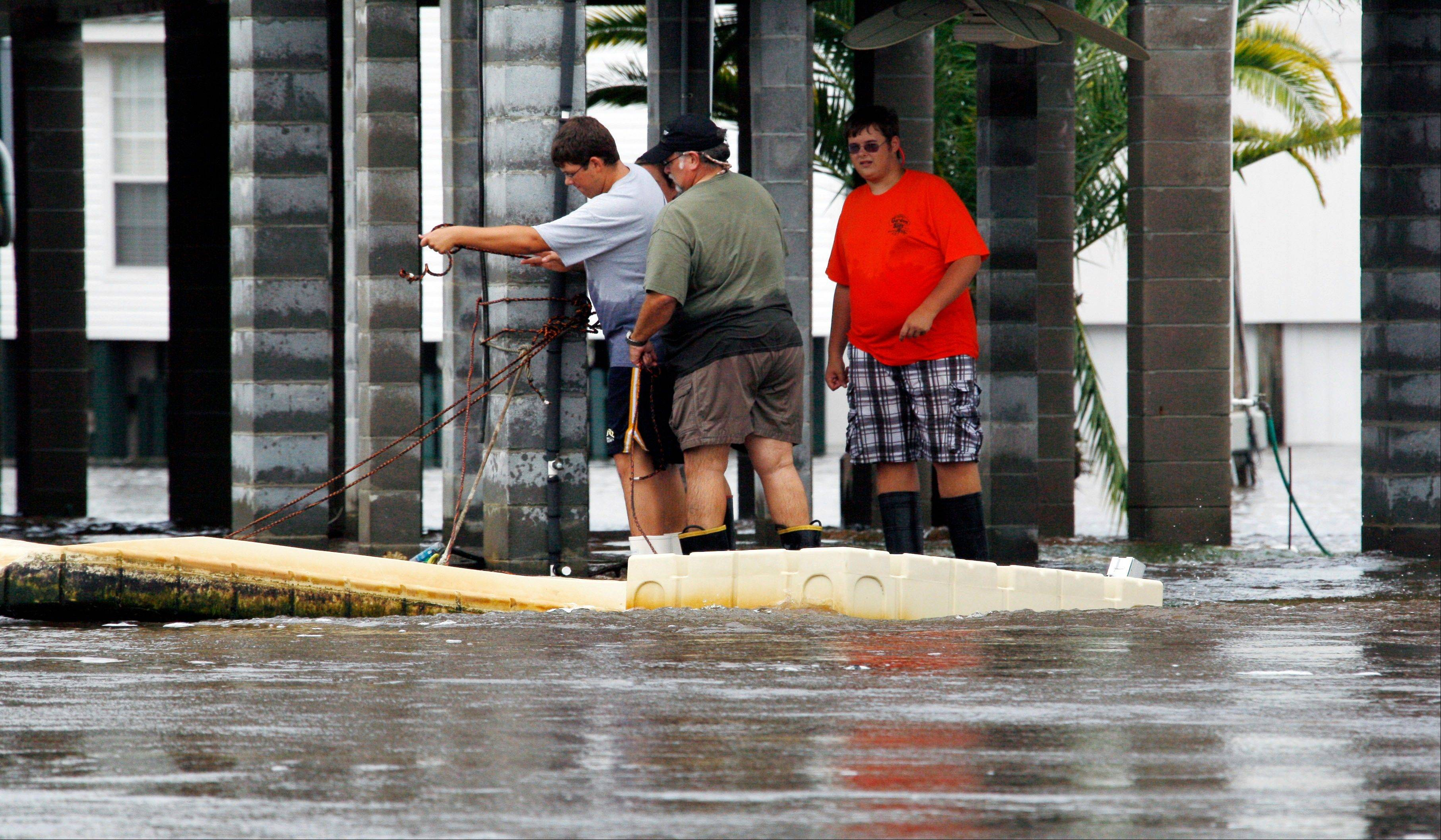 Homeowners tie a ramp Friday as several feet of moving water surround houses built on stilts on the Jourdan River in Kiln, Miss.
