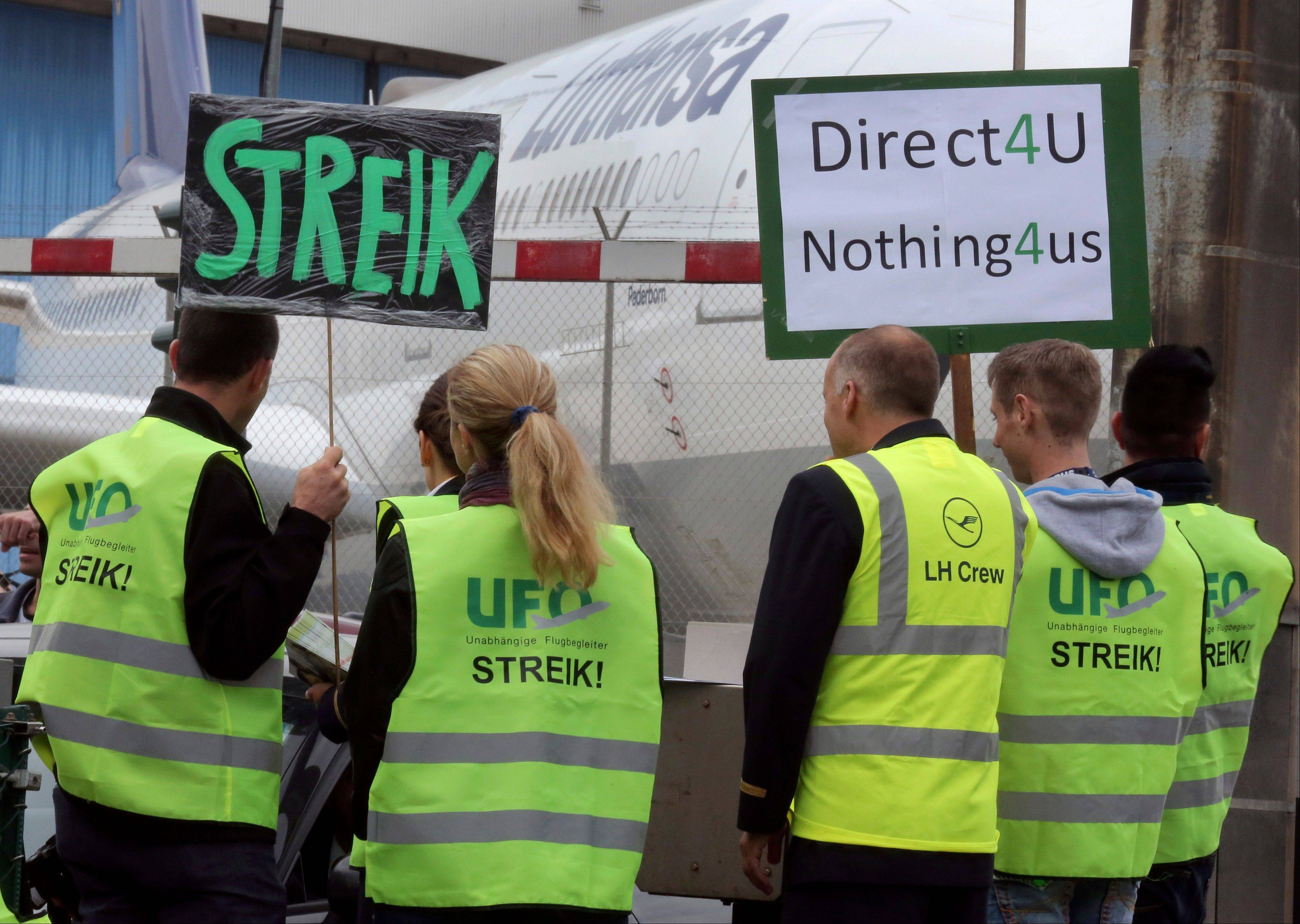 Demonstrators hold placards as they protest in front of a Deutsche Lufthansa AG aircraft at Frankfurt's Rhein-Main airport in Frankfurt, Germany, on Friday, August 31, 2012. Deutsche Lufthansa AG, Europe's second-largest airline, dropped more than half its flights today at Frankfurt airport as flight attendants staged an eight-hour strike at the carrier's main hub in a wage dispute.