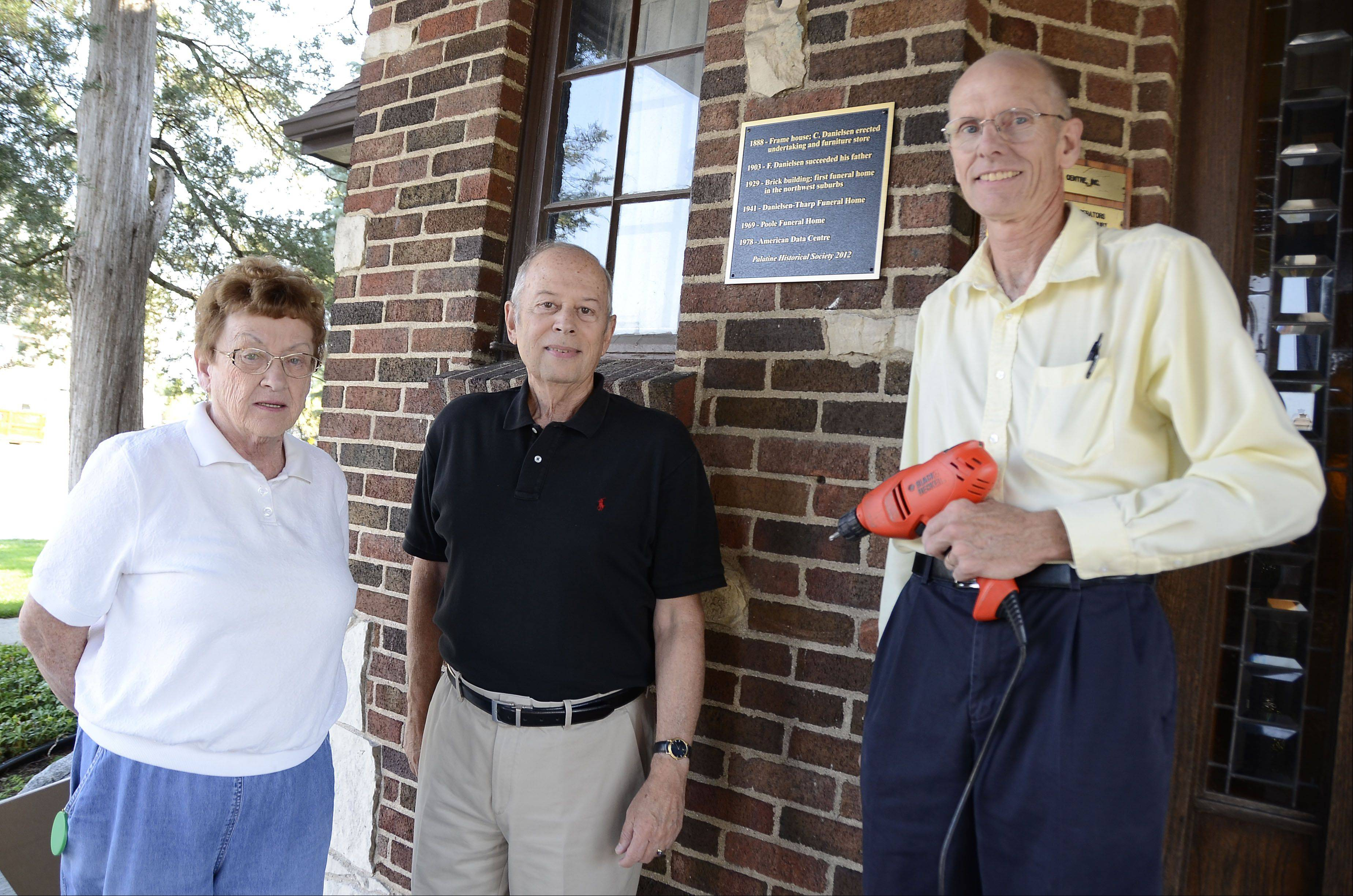 The Palatine Historical Society is erecting several plaques at sites of historical significance. Director Marilyn Pedersen, from left, American Data Centre Vice President Ronald Blum and historian David Hammer stand by the plaque they installed on Blum's building at 25 W. Palatine Road. Before the brick building was built in 1929 to house the area's first funeral home, it was a furniture store dating back to 1888.