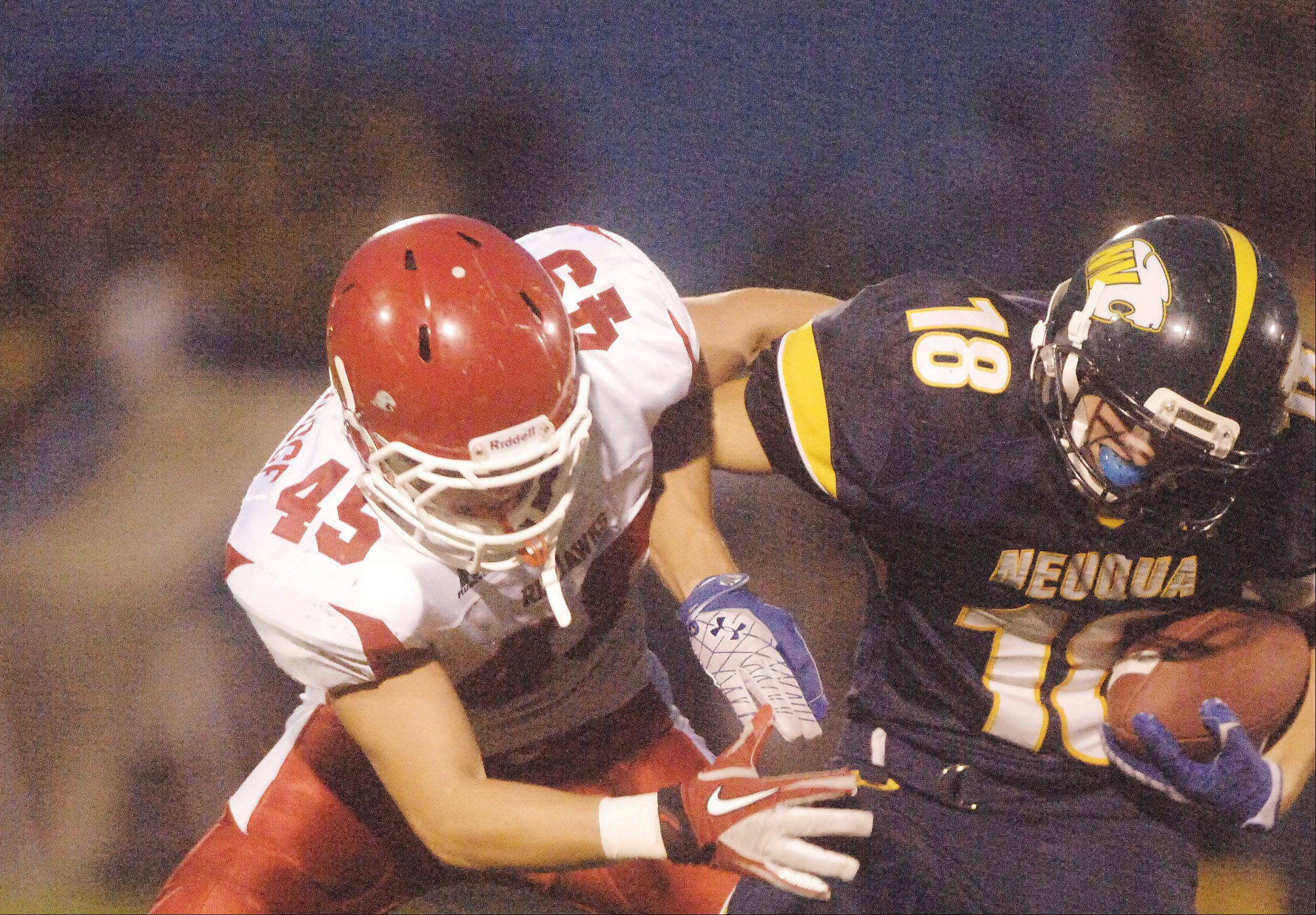 Jack Wooldridge of Naperville Central pulls down Ryan Kuhl of Neuqua Valley during Friday's nonconference game hosted by the Wildcats, who prevailed 41-28.