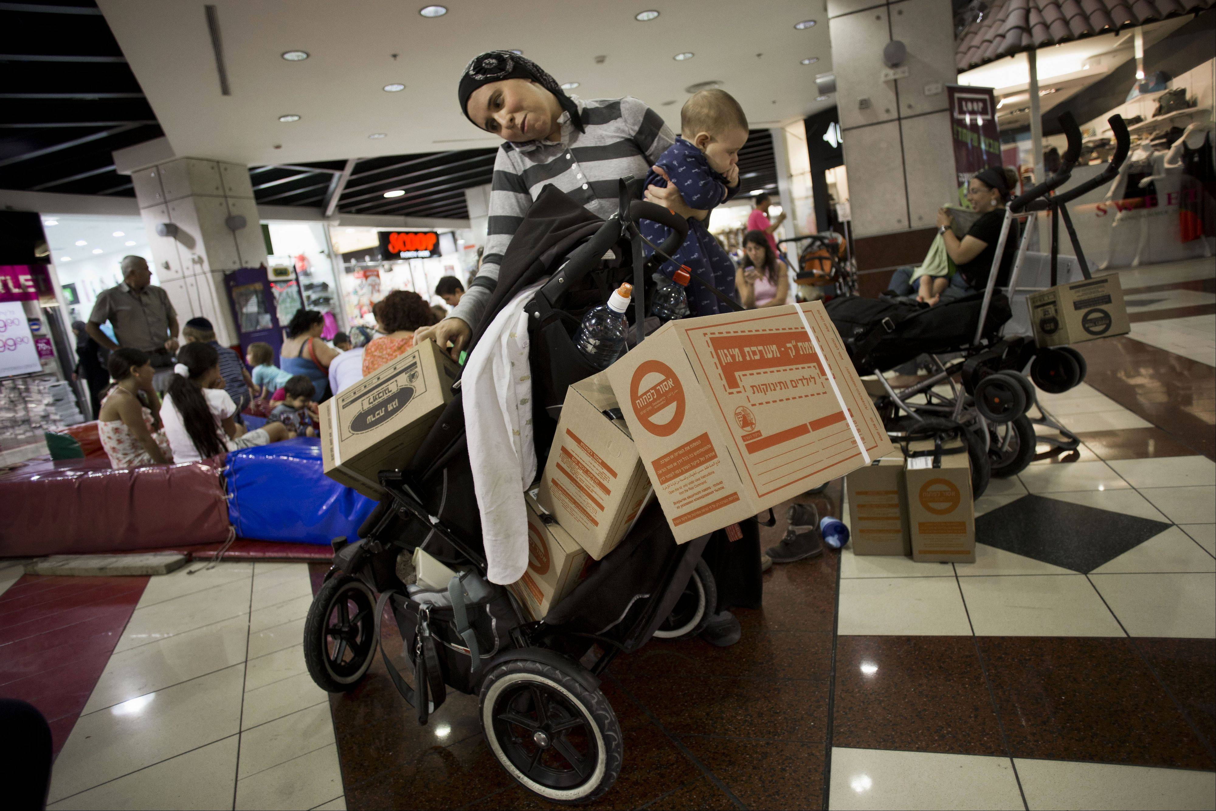 An Israeli woman talks on the phone Wednesday after collecting gas masks for her family in a shopping mall in Jerusalem.