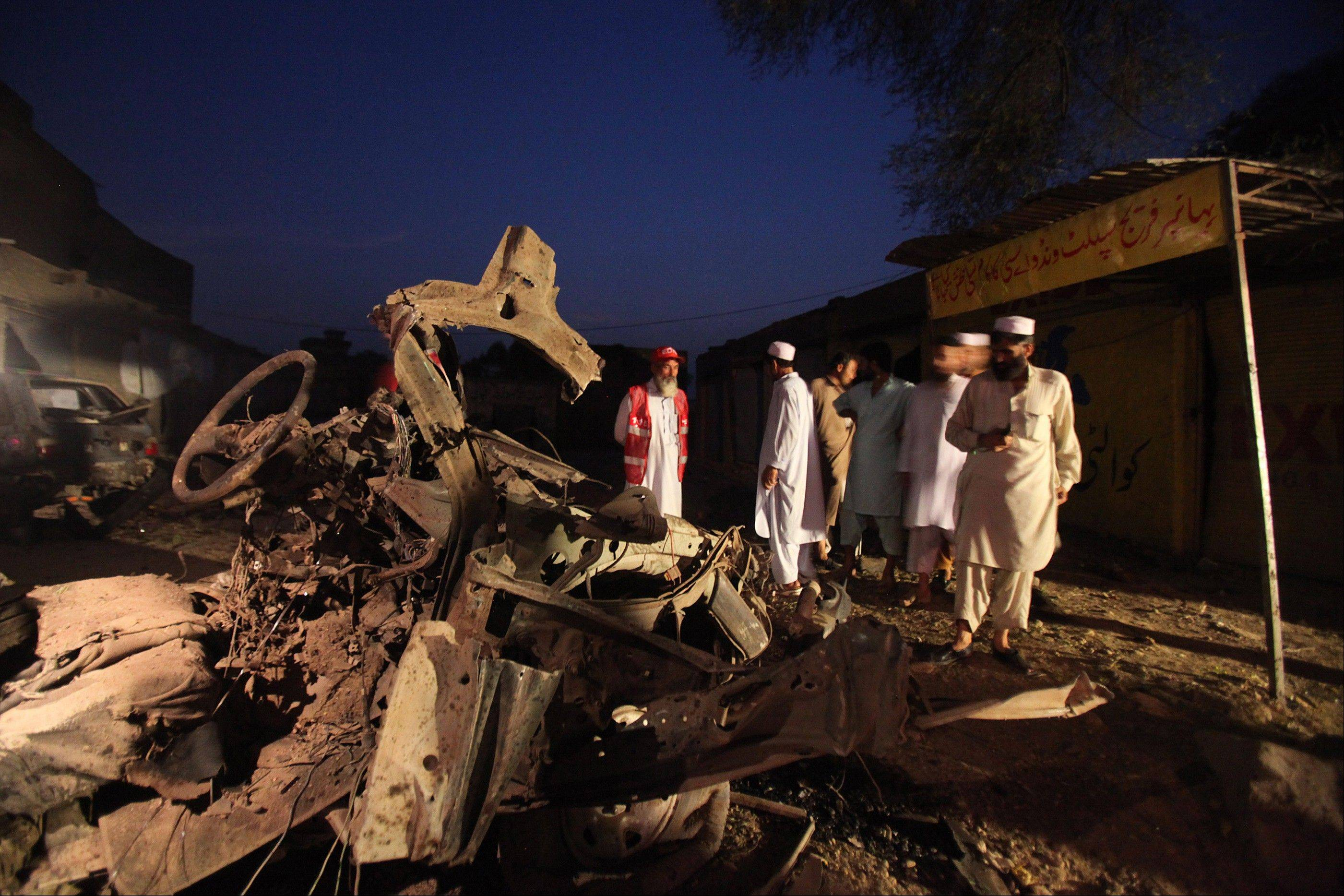 Pakistani rescue workers and investigators look at a vehicle Friday where a bomb was planted at Mattani, outside Peshawar, Pakistan.