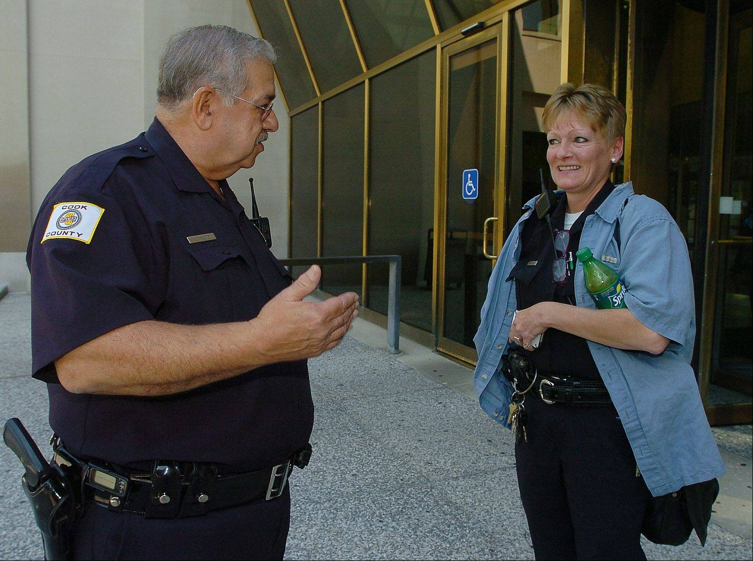 Cook County Sheriff's Deputy Stan Schultz. who's retiring after 46 years in law enforcement, chats with his partner, Deputy Mary Gersten, on his final day of work at the courthouse.