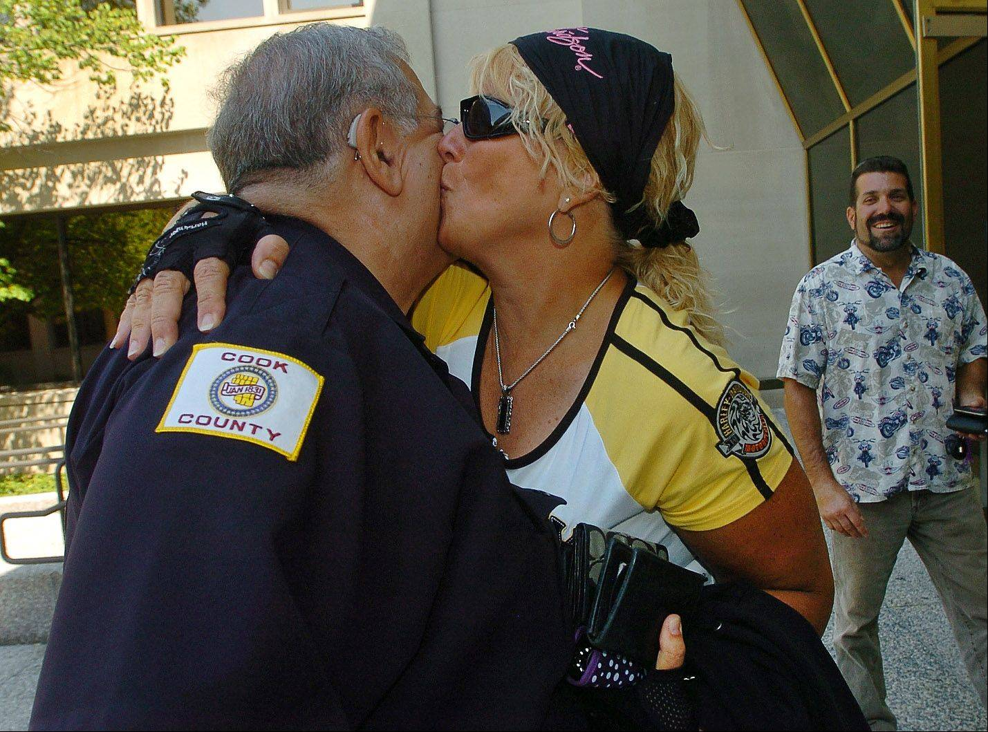 Cook County Sheriff's Deputy Stan Schultz, who's retiring after 46 years in law enforcement, gets a kiss from Probation Officer Kay Smith.