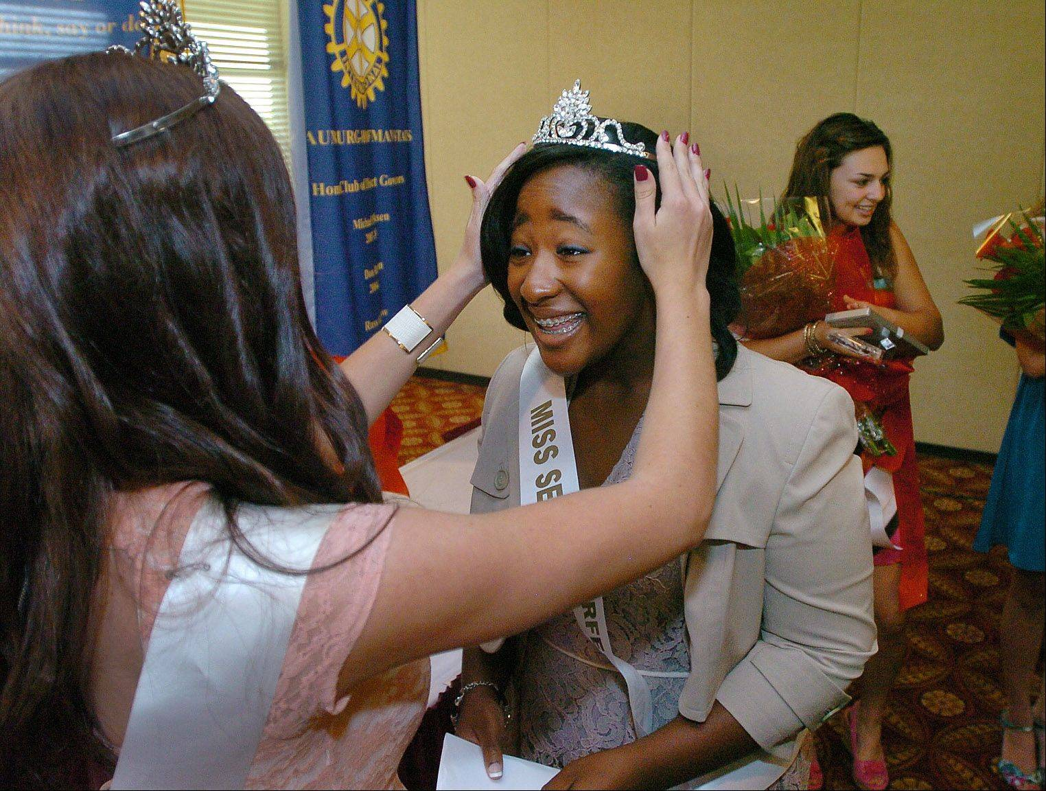 Schaumburg's Miss Septemberfest 2011 Ali Roller, left, crowns Mariah Ghant of Conant High School as Miss Septemberfest 2012 at Bridges of Poplar Creek Country Club in Hoffman Estates Friday.