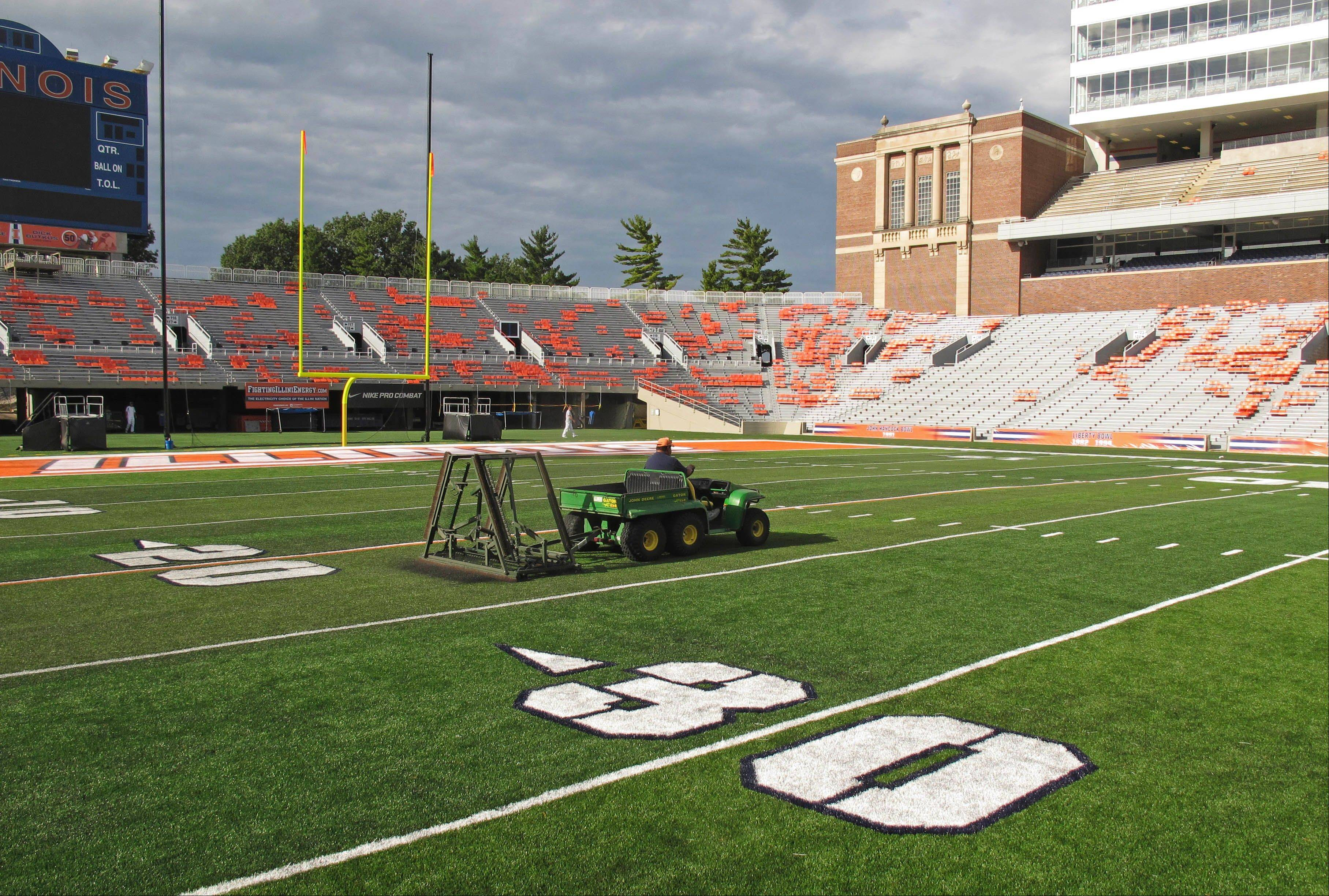 University of Illinois employee Ron Luna grooms the artificial turf Friday at Memorial Stadium in Champaign Illinois is scheduled to open the NCAA college football season on Saturday against Western Michigan. Forecasters say there could be a soaking that produces 6 to 8 inches or more of rain. But school officials say the brand-new turf can drain about 10 inches of rain an hour.