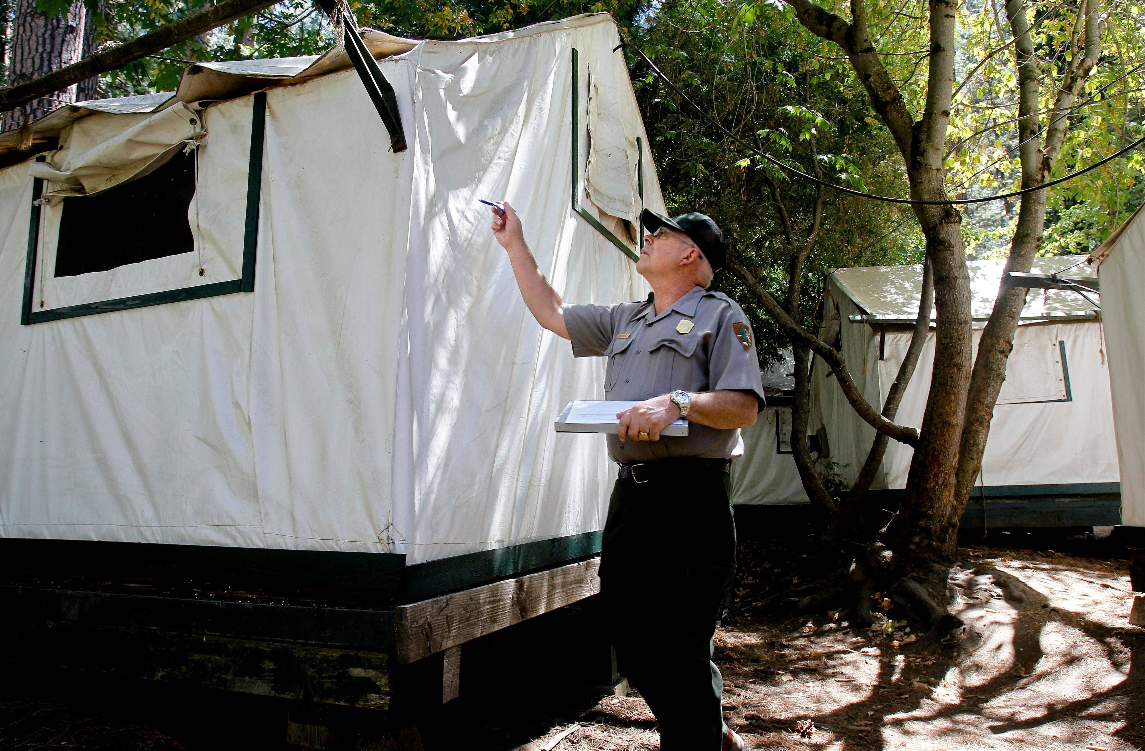 Glenn Dean, a National Parks Occupational Safety and Health Specialist, inspects tent cabins Tuesday for mice entry points at Curry Village at Yosemite National Park.