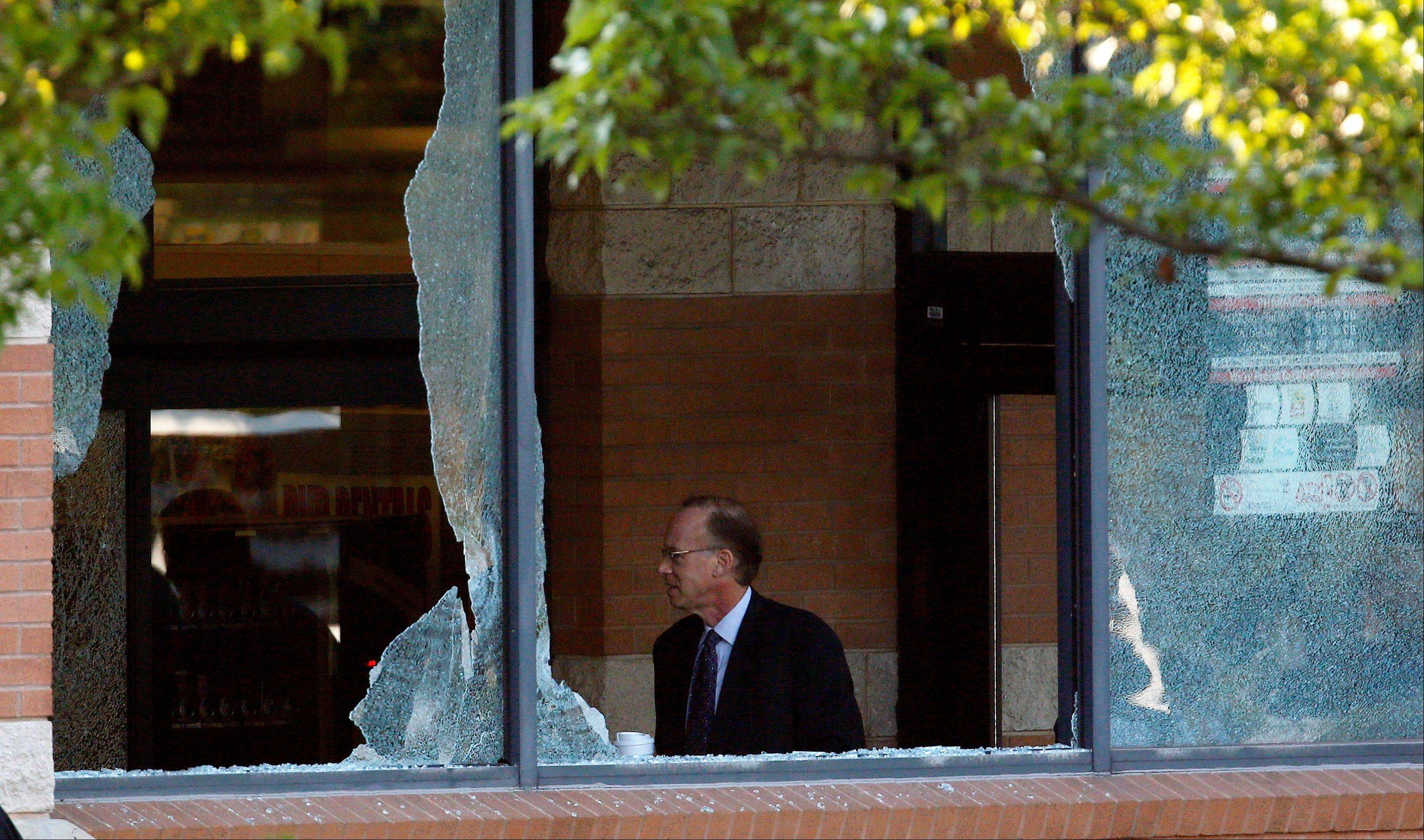Middlesex County prosecutor Bruce Kaplan is seen through two broken windows as he arrives at the scene of a shooting at a Pathmark grocery store in Old Bridge, N.J., Friday, Aug. 31, 2012. At least three people have died in the shooting. A law enforcement official briefed on the shooting says the person believed to be the shooter is among the dead.