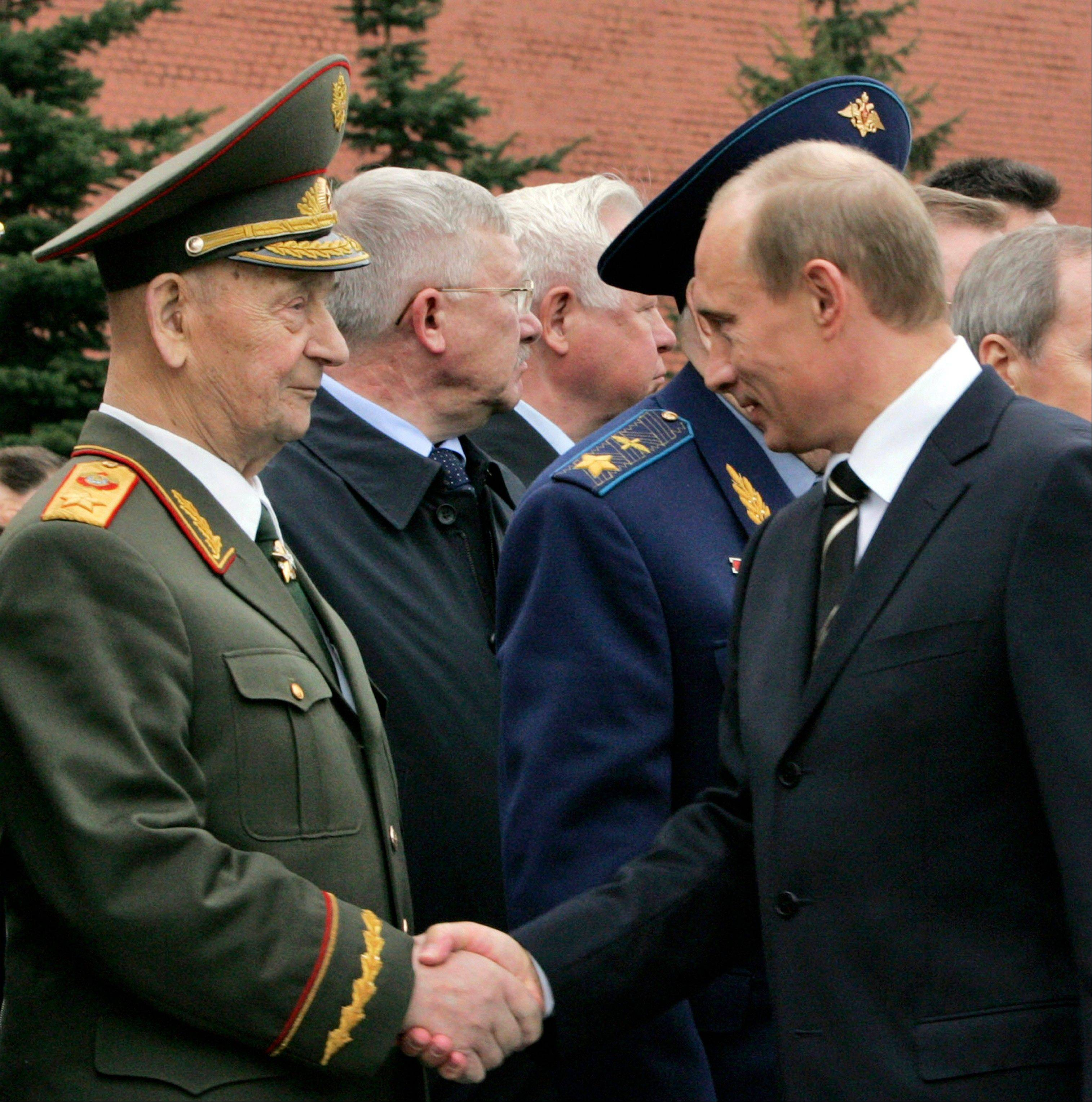 In this 2007 file photo, former Soviet Defense Minister, Marshal Sergei Sokolov, left, shakes hands with Russian President Vladimir Putin, right. Sergei Sokolov, the Soviet defense minister fired by the Politburo after a German teenager landed his plane on Moscow's Red Square in the 1980s, has died. He was 101.