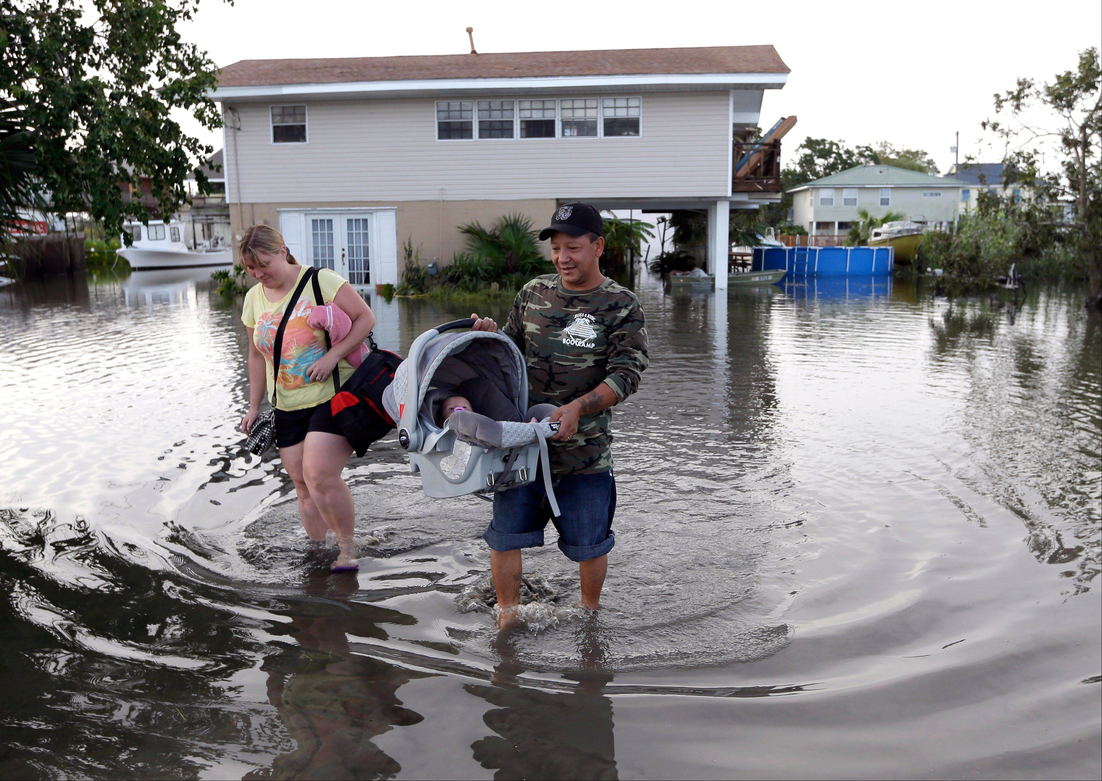 Tony Rodriguez, right, carries his baby daughter Nicole as they and his wife Jodi Clelland leave their flooded home in the aftermath of Hurricane Isaac in Slidell, La., Friday, Aug. 31, 2012. Isaac is now a tropical depression and the center was on track to cross Arkansas on Friday and southern Missouri on Friday night, spreading rain as it goes.