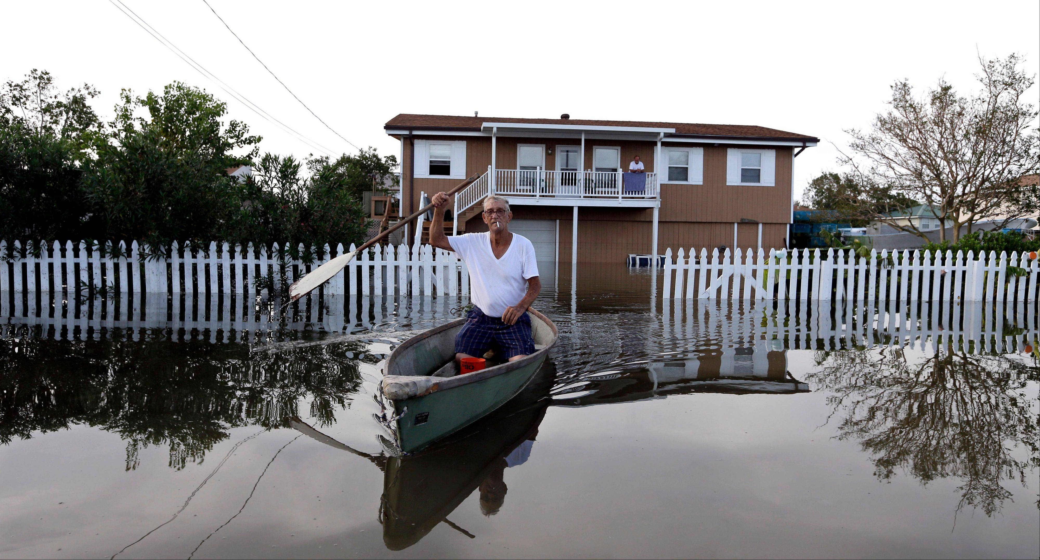Anthony Segrave rides in his boat as he leaves his son's flooded home in the aftermath of Hurricane Isaac in Slidell, La., Friday, Aug. 31, 2012. Isaac is now a tropical depression and the center was on track to cross Arkansas on Friday and southern Missouri on Friday night, spreading rain as it goes.