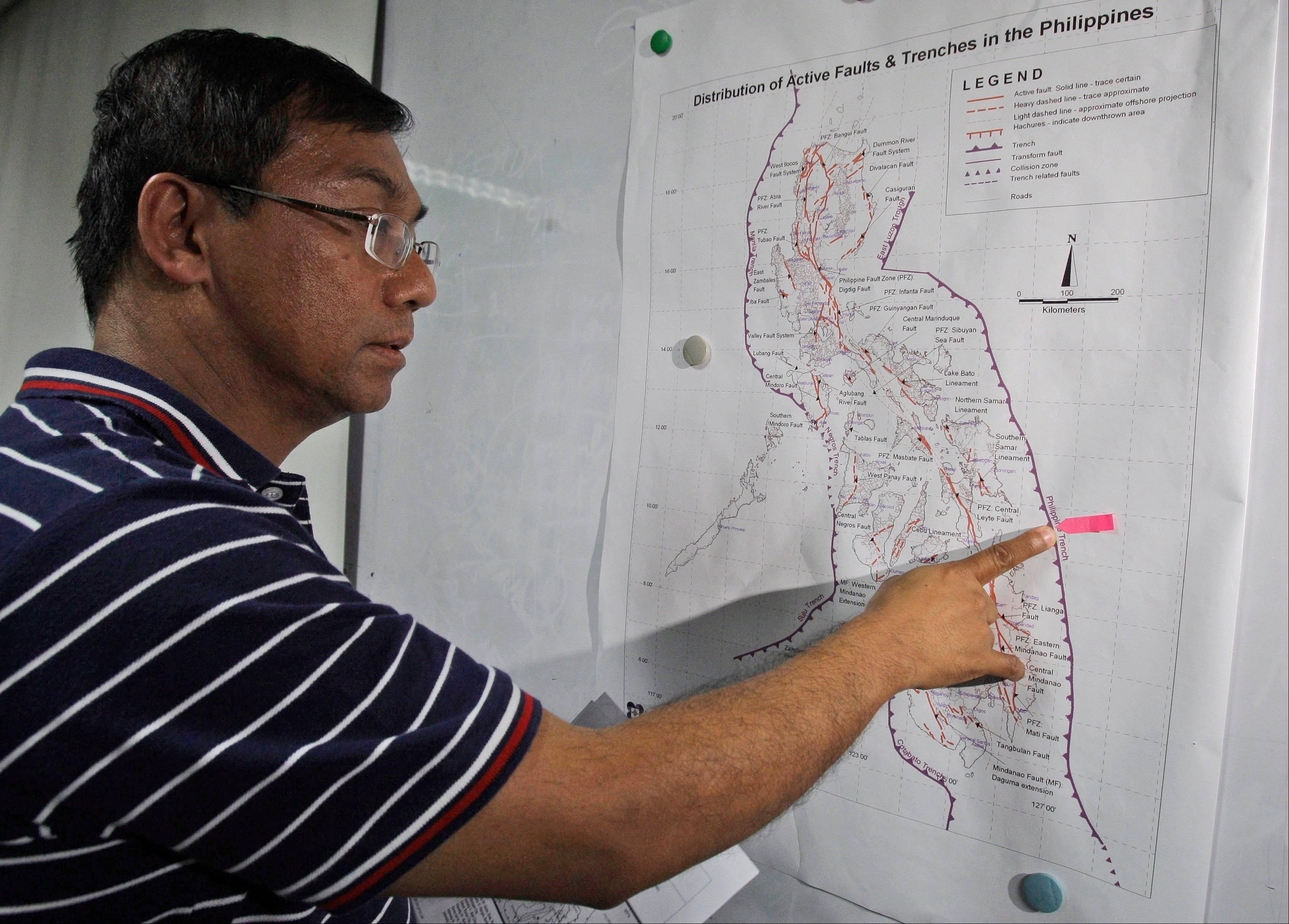 Renato Solidum, head of the Philippine seismology agency, points to an area on a Philippine map where the epicenter of the earthquake happened during a press conference in suburban Quezon City, north of Manila, Philippines on Friday Aug. 31, 2012. A 7.6-magnitude quake struck off the eastern coast of the Philippines late Friday, killing at least one person in a house collapse and setting off small tsunami waves about 0.1-foot-high. Most coastal residents fled to high ground and power was knocked out in several cities.