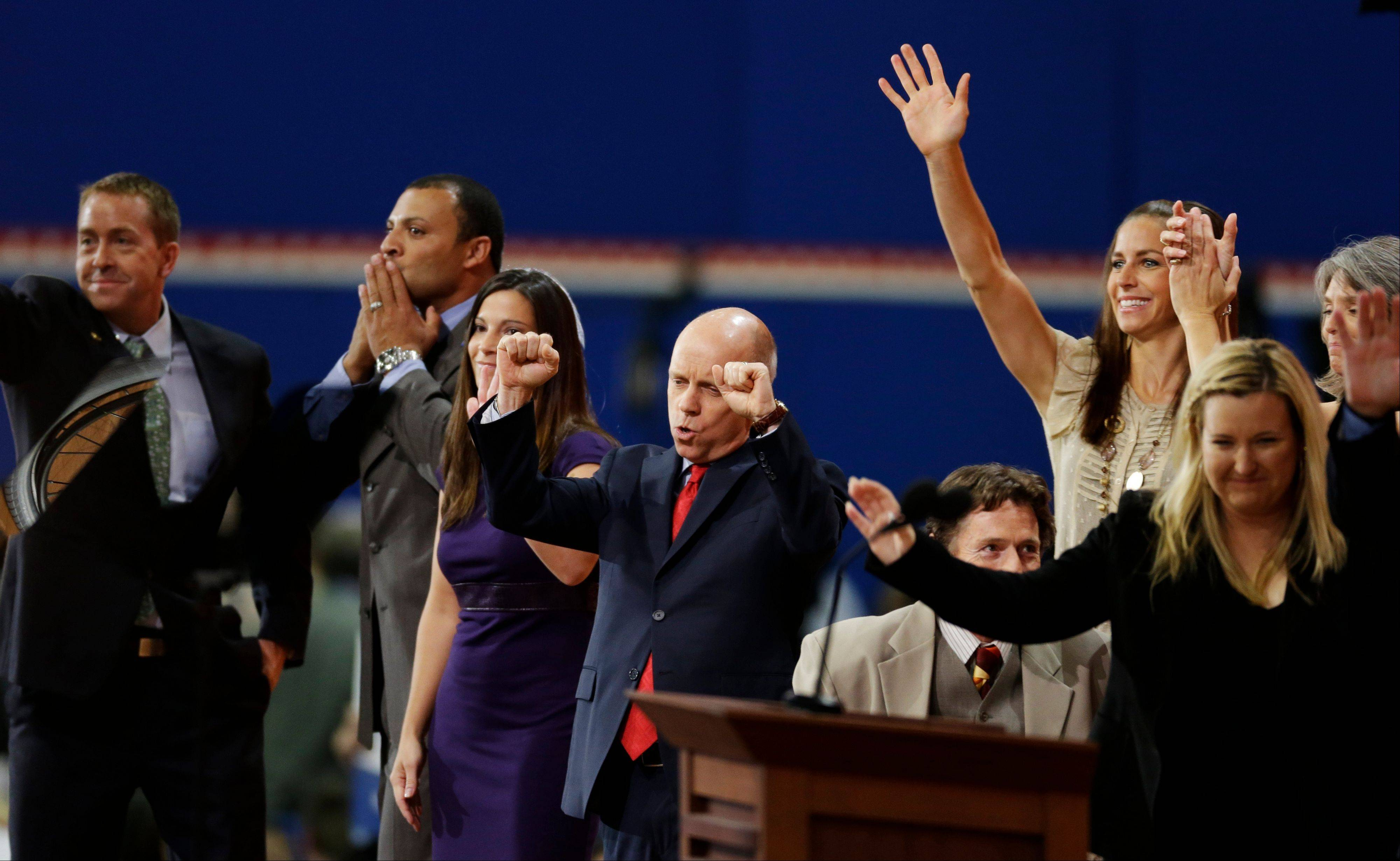 Figure skater Scott Hamilton and other Olympians cheer after gold medalist Kim Rhode's, right, speech to delegates during the Republican National Convention in Tampa, Fla., on Thursday, Aug. 30, 2012.