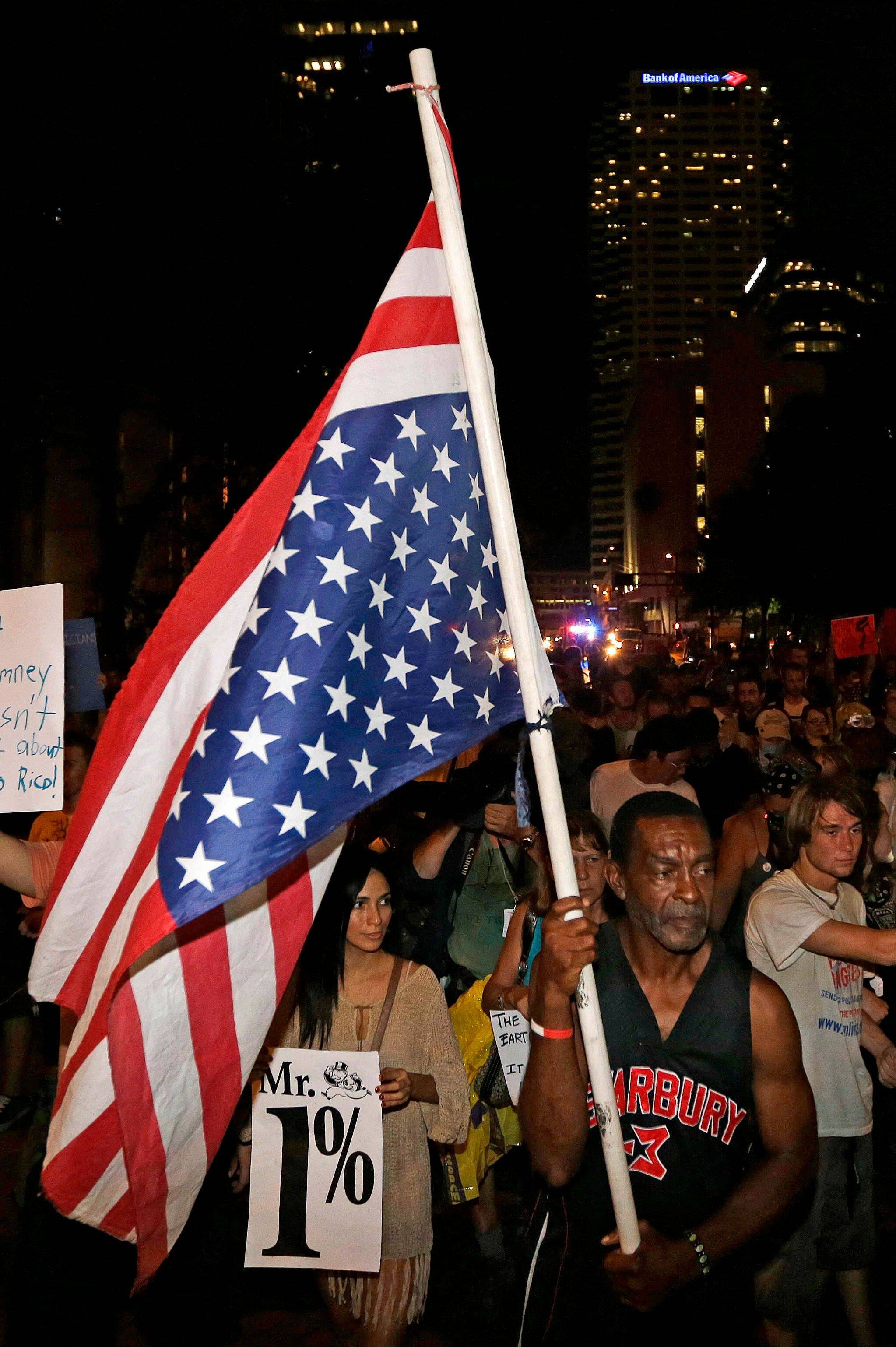 Demonstrators chant during a protest march while using a puppet in the likeness of Mitt Romney, Thursday, Aug. 30, 2012, in Tampa, Fla. Protestors gathered in Tampa to march in demonstration against the Republican National Convention.