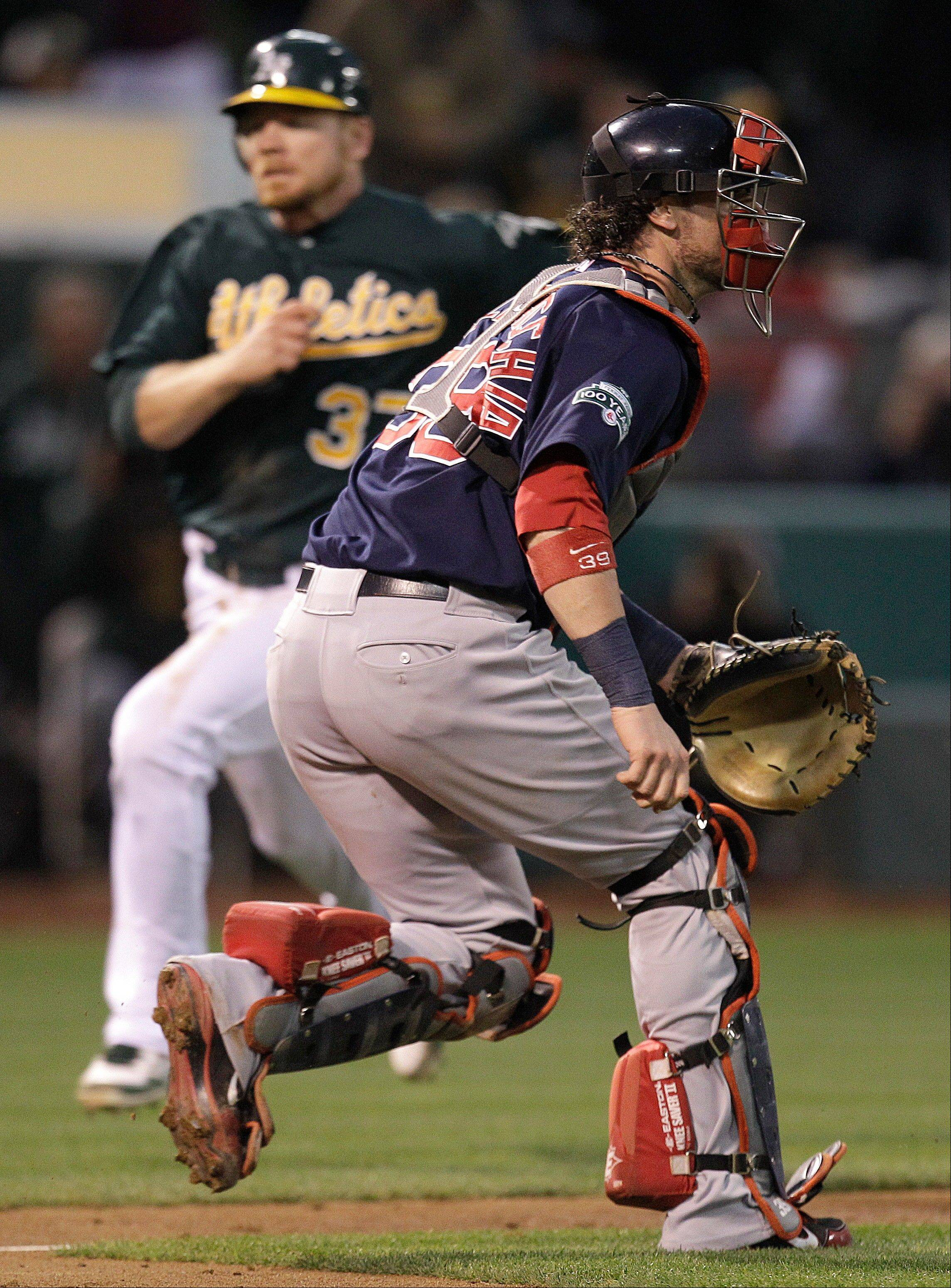 Oakland's Brandon Moss scores as Boston catcher Jarrod Saltalamacchia waits for the ball in the second inning Friday in Oakland, Calif.