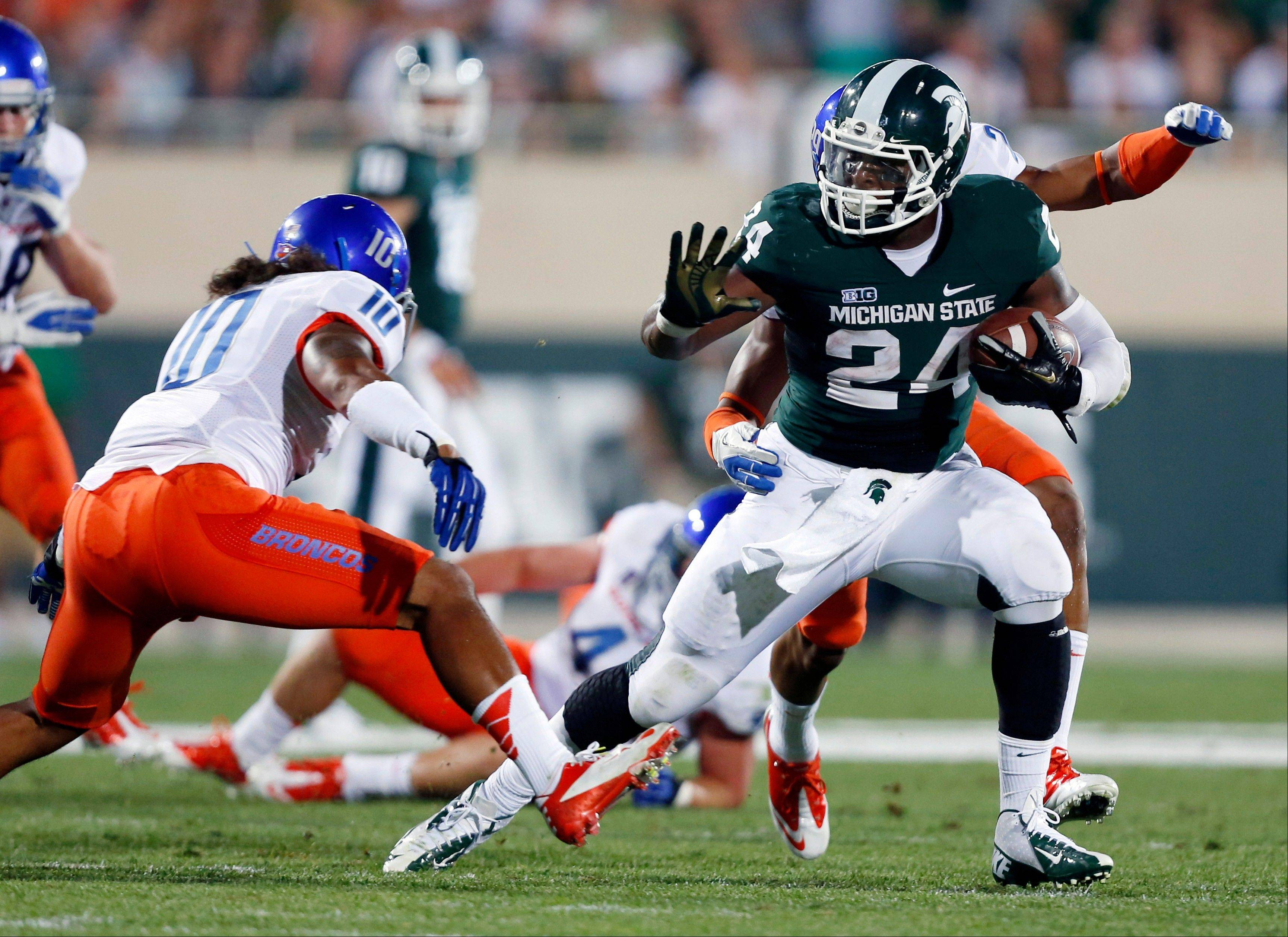 Michigan State's Le'Veon Bell, right, rushes against Boise State's Jeremy Ioane during the first quarter Friday in East Lansing, Mich.