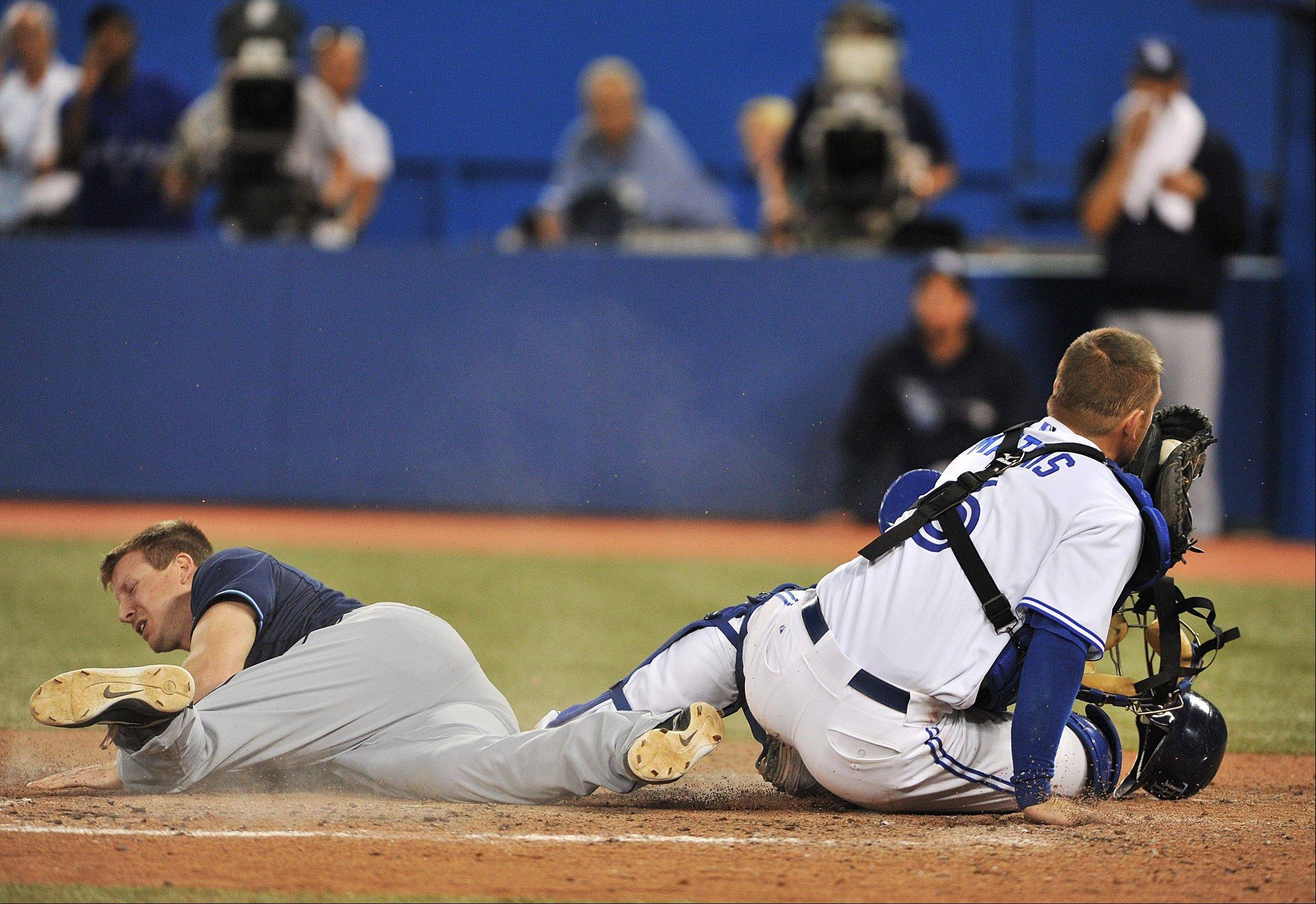 The Rays' Elliot Johnson, left, is laid out by Blue Jays catcher Jeff Mathis after attempting to score in the ninth inning Friday in Toronto.