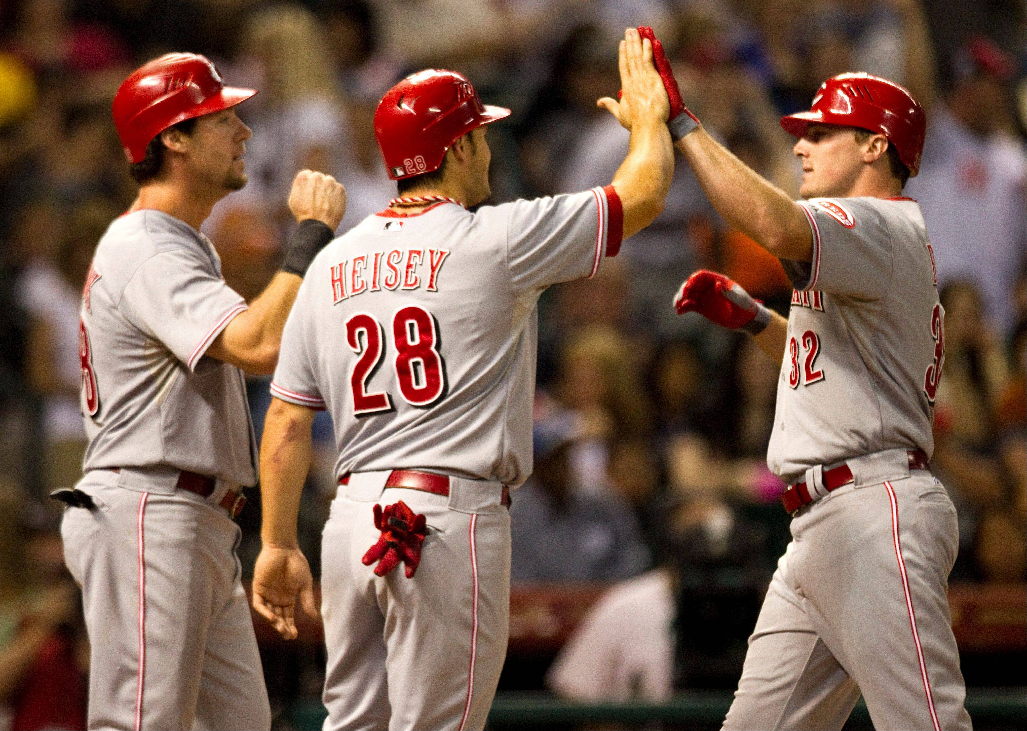 Reds right fielder Jay Bruce (32) is met at the plate by teammates Ryan Ludwick, left, and Chris Heisey after hitting a three-run home run during the fifth inning Friday in Houston.