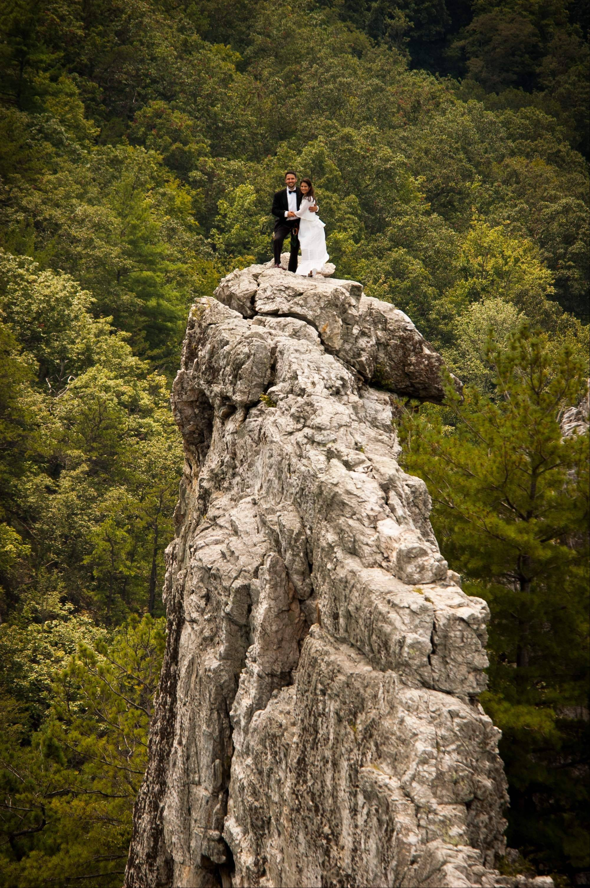 Bob Ewing, 32, right, and Antonie Hodge, 30, both of Arlington, Va., pose at Seneca Rocks in W.Va. The couple made the 900-foot climb in formal wedding attire.