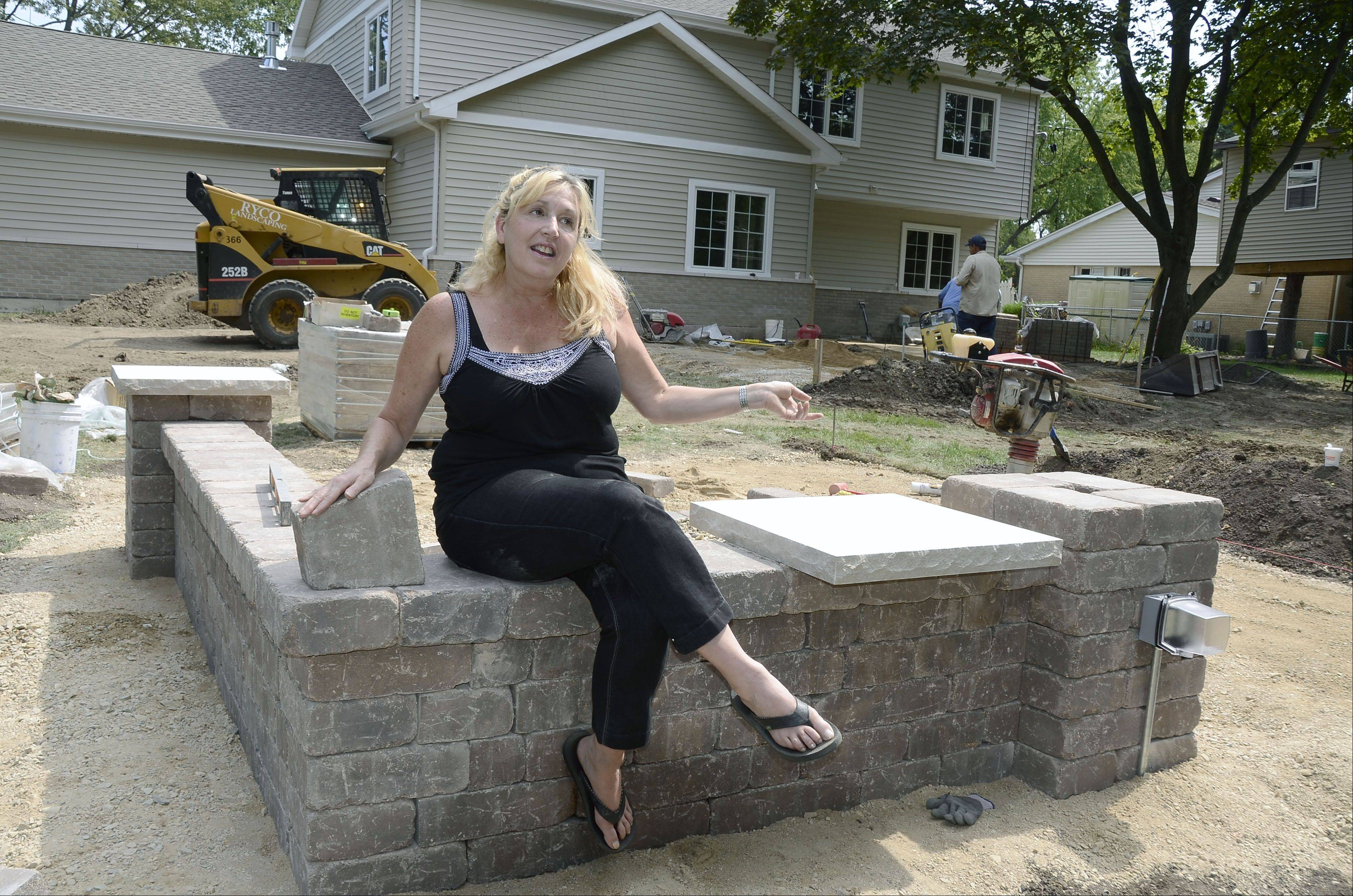 Sharon Zeeck sits on the beginnings of the new wall sheltering a fire pit in the backyard of her Prospect Heights home and points to the area where a pond will be built.