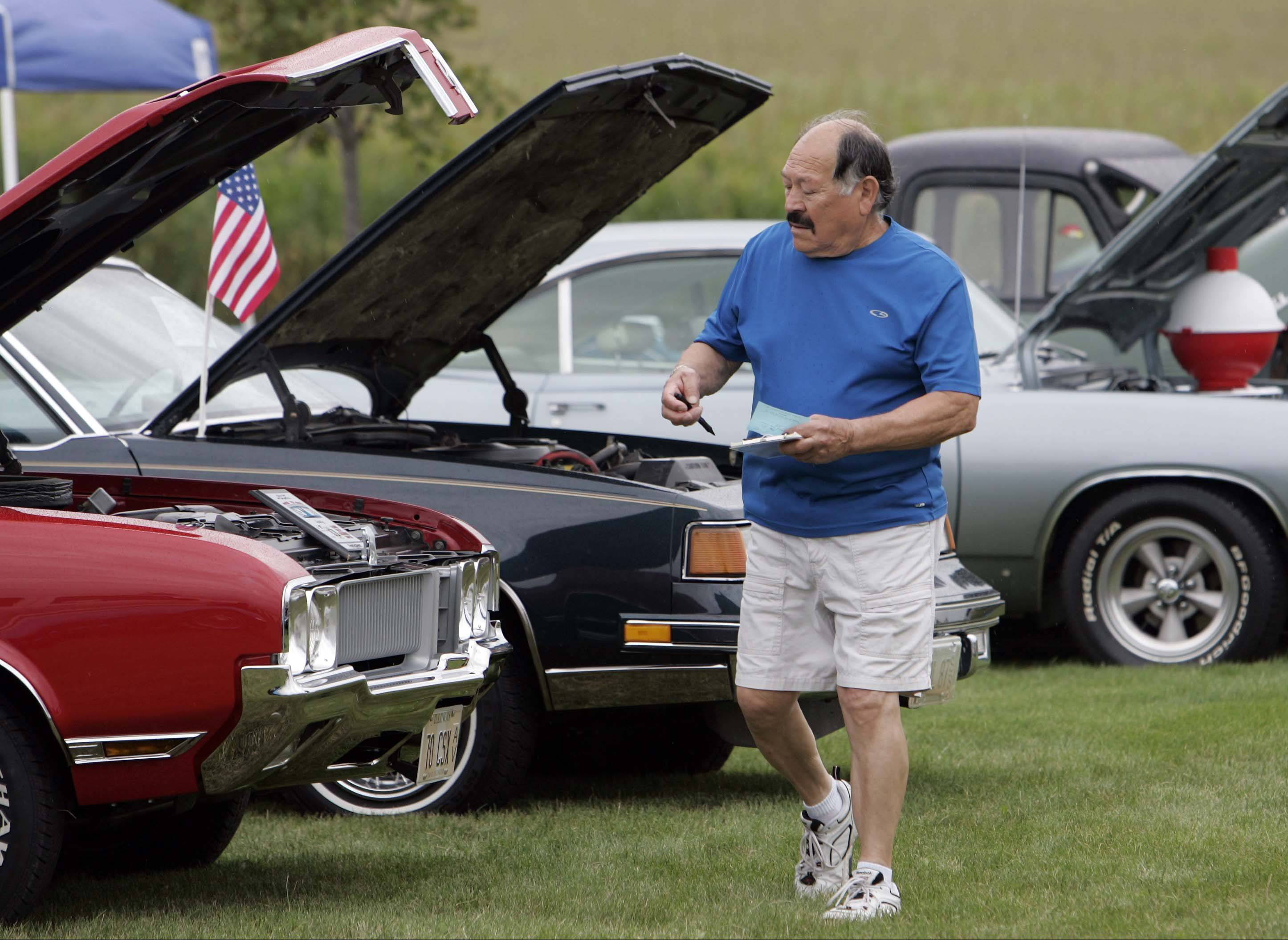 Lee Gomez of St. Charles gets a look at the cars during Kane County Sheriff Pat Perez�s sixth annual charity car and motorcycle show Saturday in Elburn. Gomez was showing his six-cylinder 1965 Chevrolet Impala.