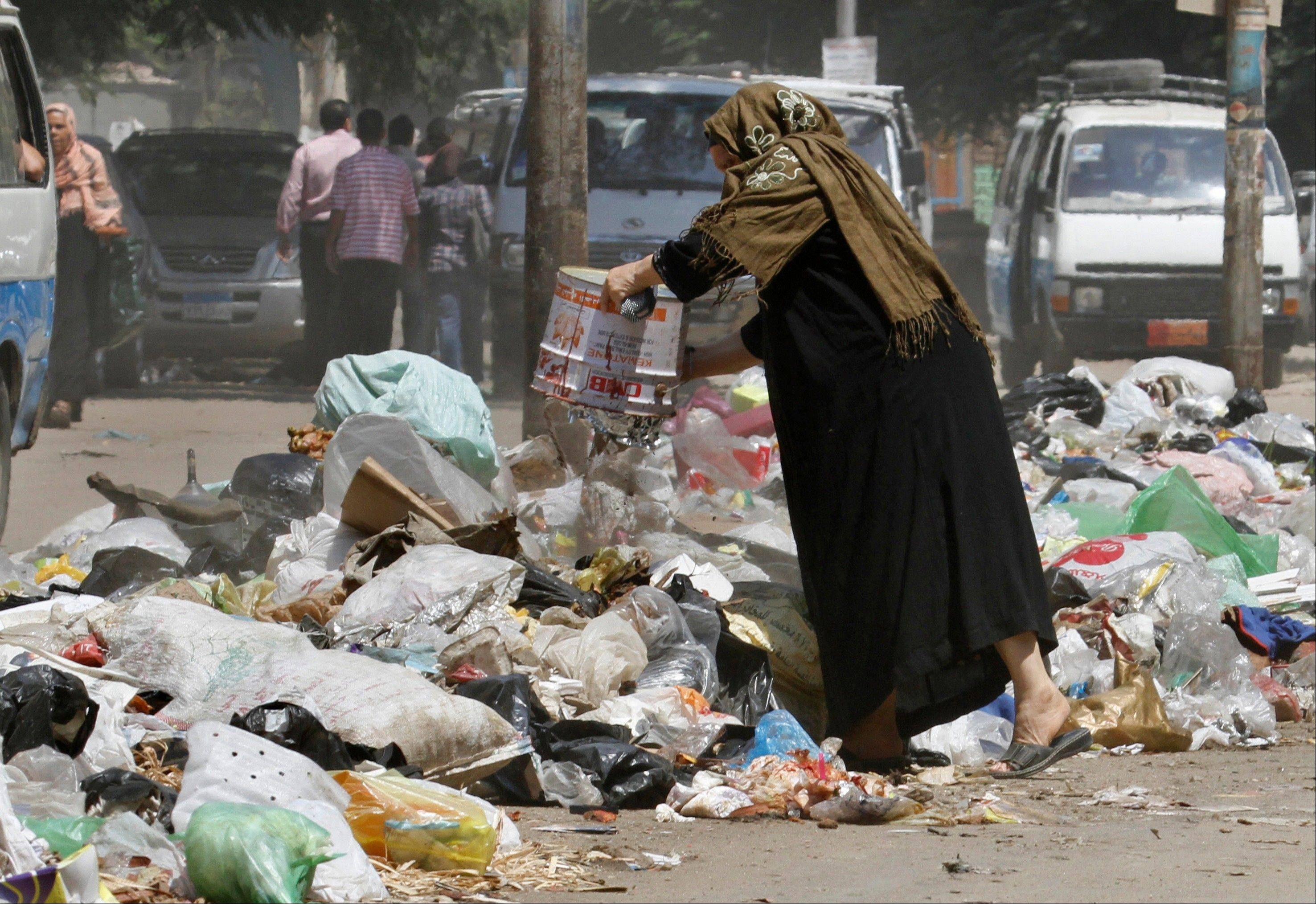 A woman throws her waste in a street in Cairo.