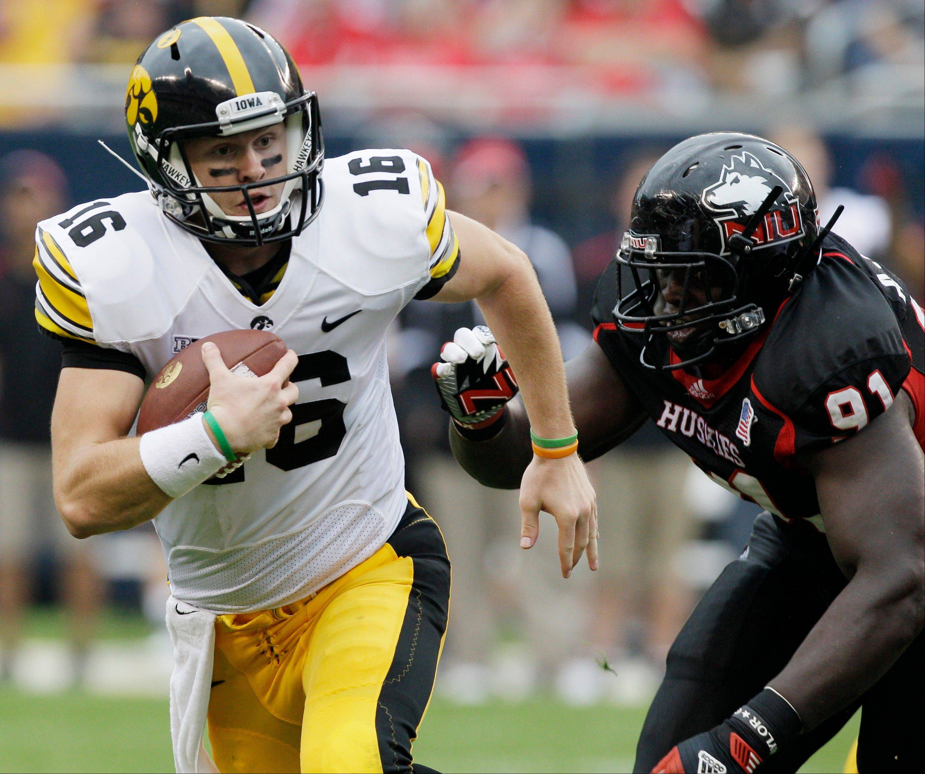 Iowa quarterback James Vandenberg (16) runs with the ball past Northern Illinois defensive line Anthony Wells (91) during the first half of an NCAA college football game at Soldier Field in Chicago, Saturday, Sept. 1, 2012.