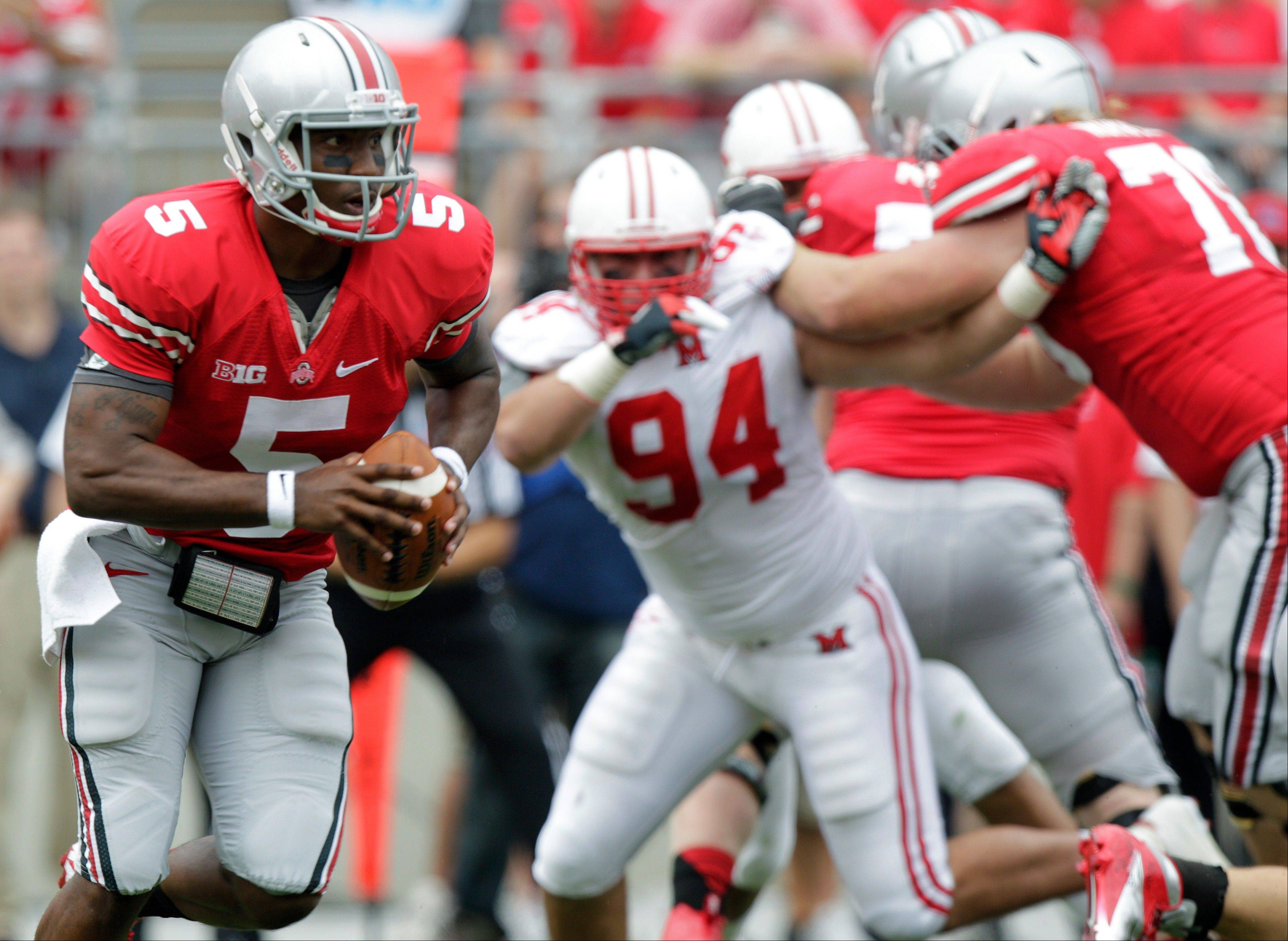 Ohio State�s Braxton Miller, left, runs an option play against Miami of Ohio during the first quarter of an NCAA college football game Saturday in Columbus, Ohio. Miller rushed for 161 yards, a record for an Ohio State quarterback, and threw for two scores in their 56-10 win.