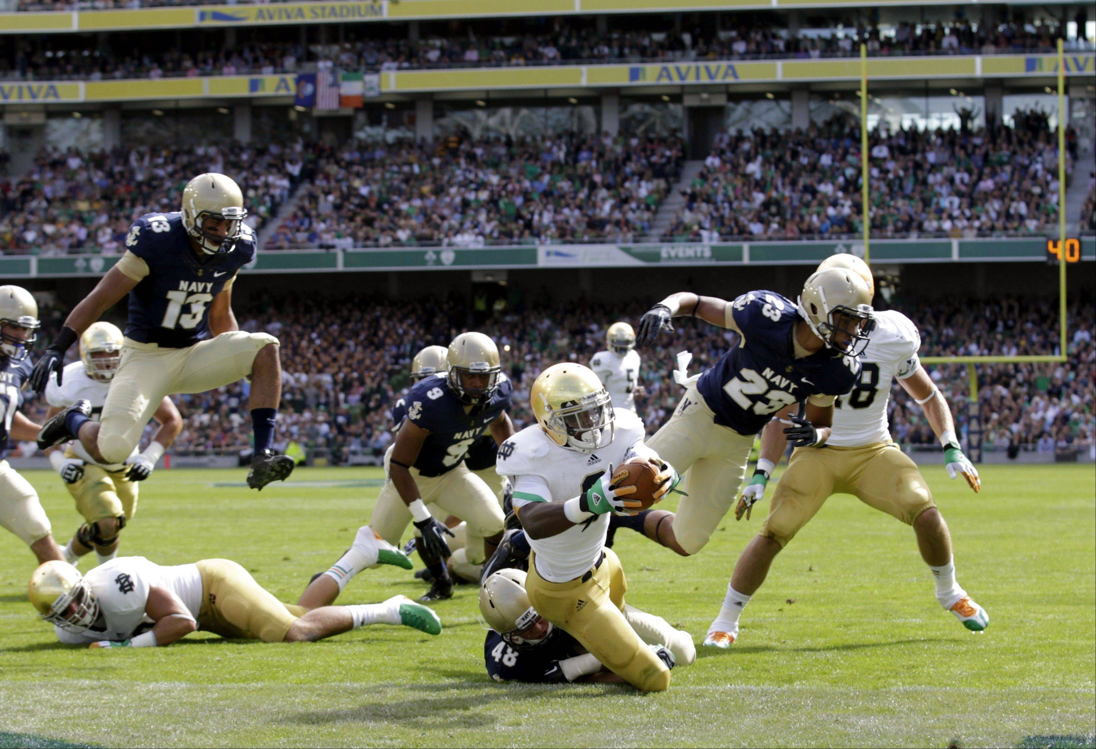 Notre Dame�s Theo Riddick, centre, scores a touchdown, as he is tackled by Navy�s Keegan Wezel during their NCAA college football game in Dublin, Ireland, Saturday, Sept. 1.