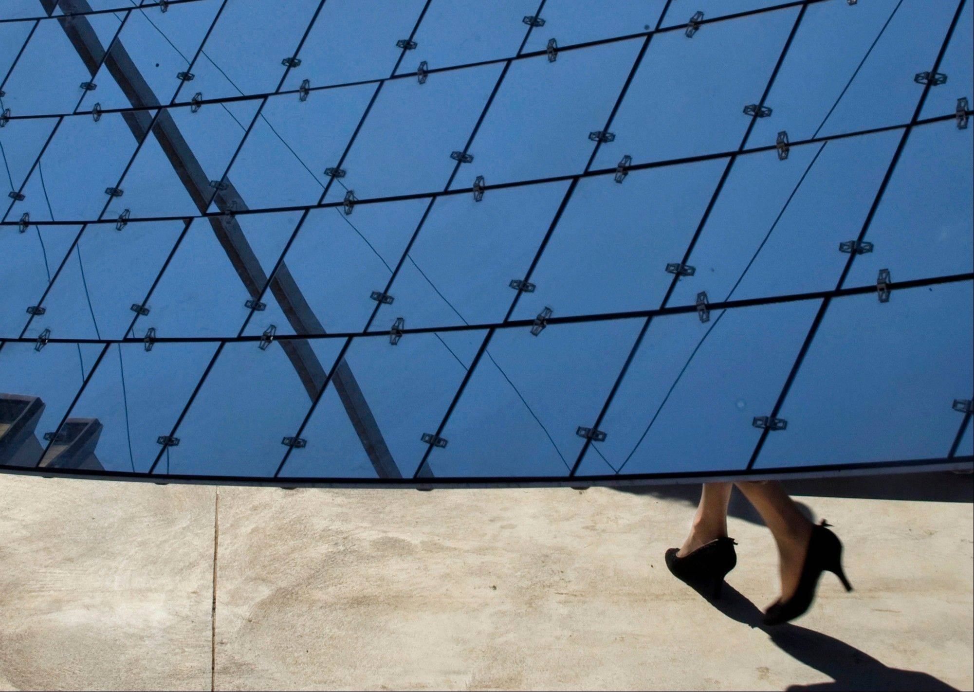 A visitor walks by a solar dish at a solar farm, which according to the manufacturer, are revolutionary in the way they efficiently produce maximum energy using a minimal area, in Kibbutz Kvutzat Yavne, Israel.