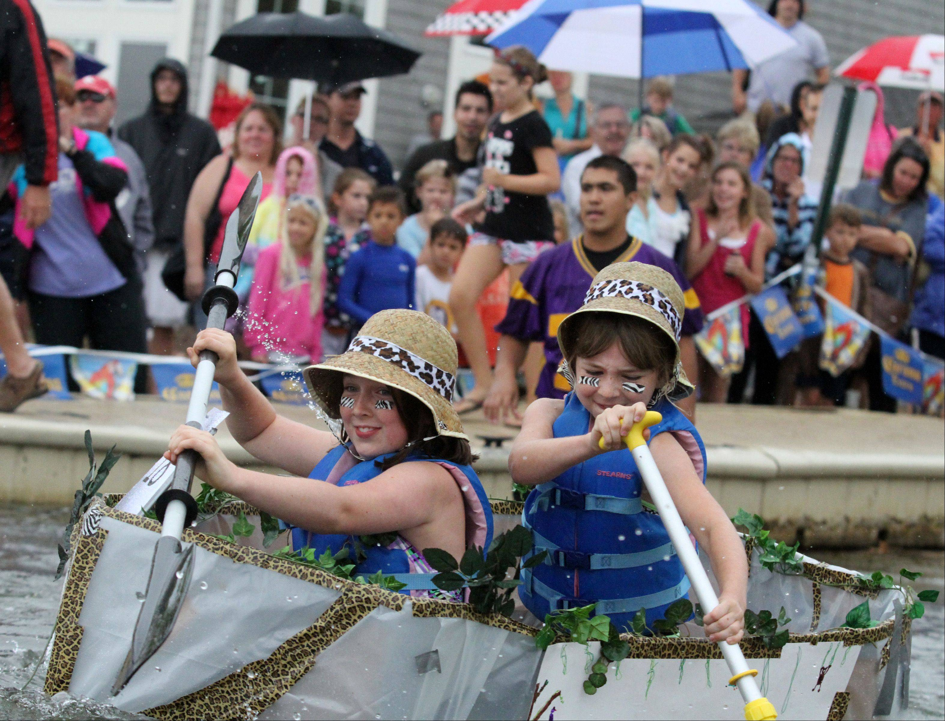 Olivia Holsen, 10, and her sister, Amanda, 8, both of Hawthorn Woods, paddle to victory Saturday at the 11th Annual Cardboard Boat Races at Lindy's Landing on Bangs Lake in Wauconda.