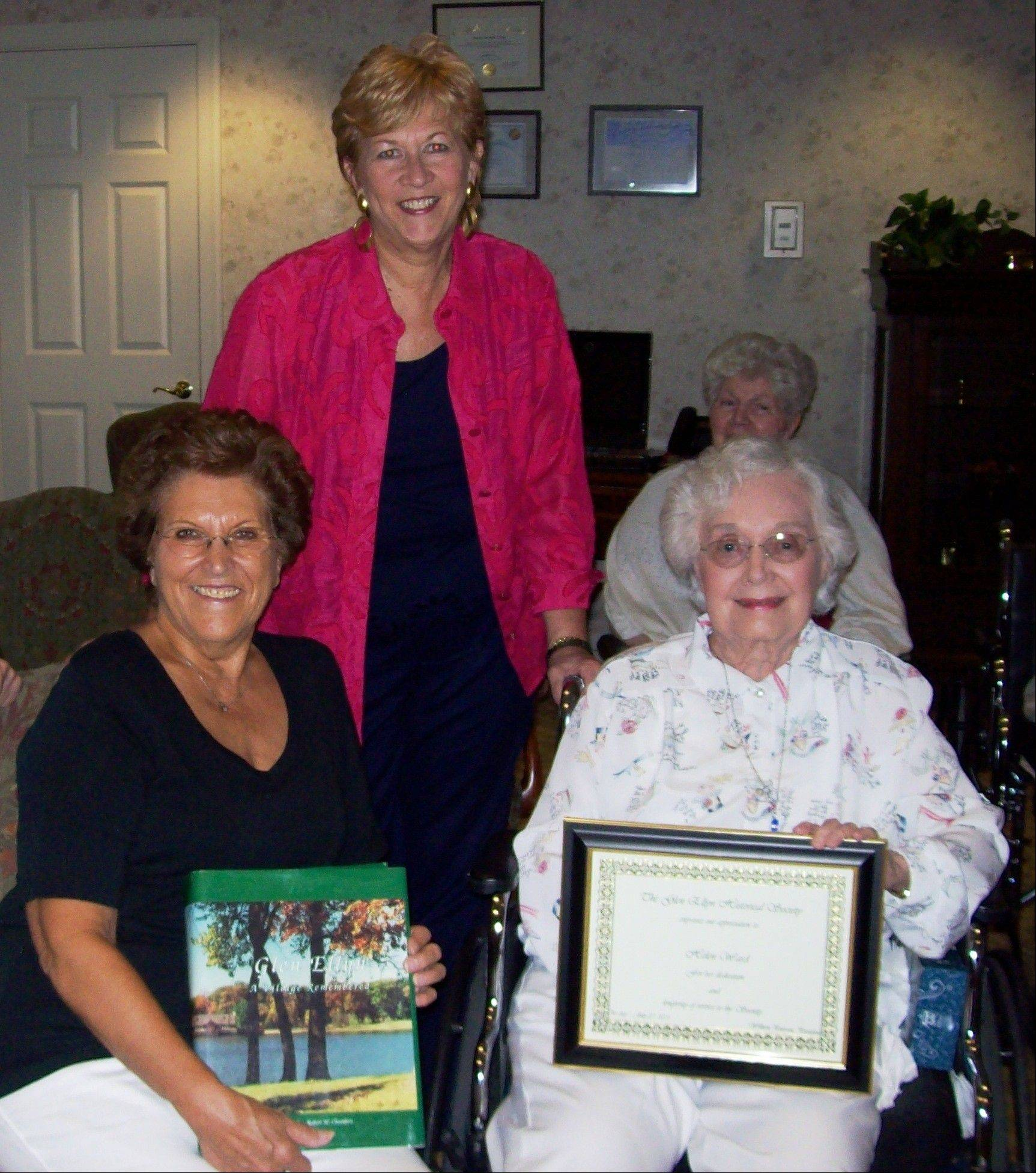 "Helen Ward, right, received the Glen Ellyn Historical Society's service award in 2011 from president Ruth Wright, left holding a copy of ""Glen Ellyn: a Community Remembered,"" and past executive director Jane Rio, center."