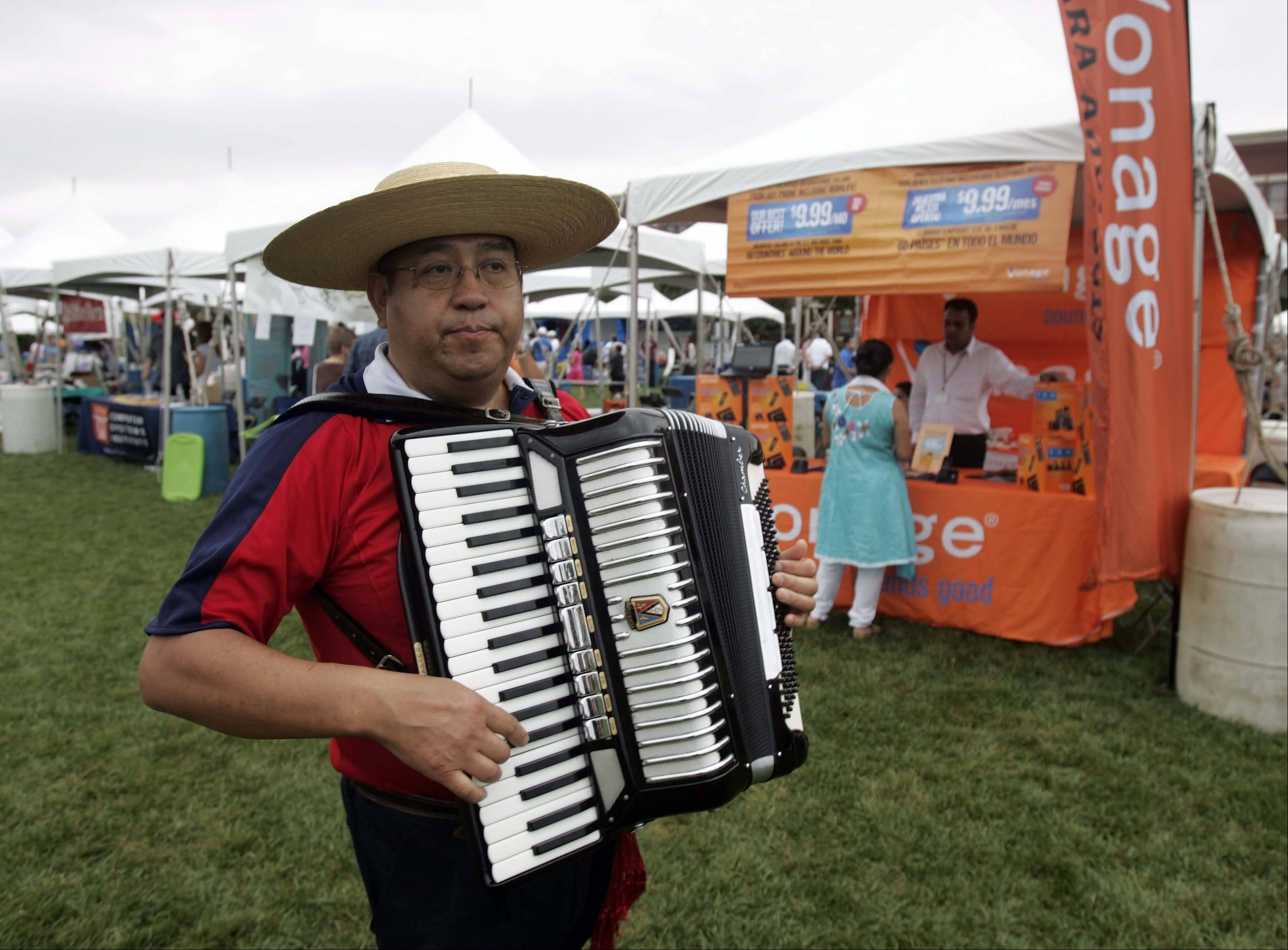 Henoch Fuentes of Elgin makes his way to the stage as he plays the national anthem of Chile during Elgin's first international festival at Festival Park in Elgin.