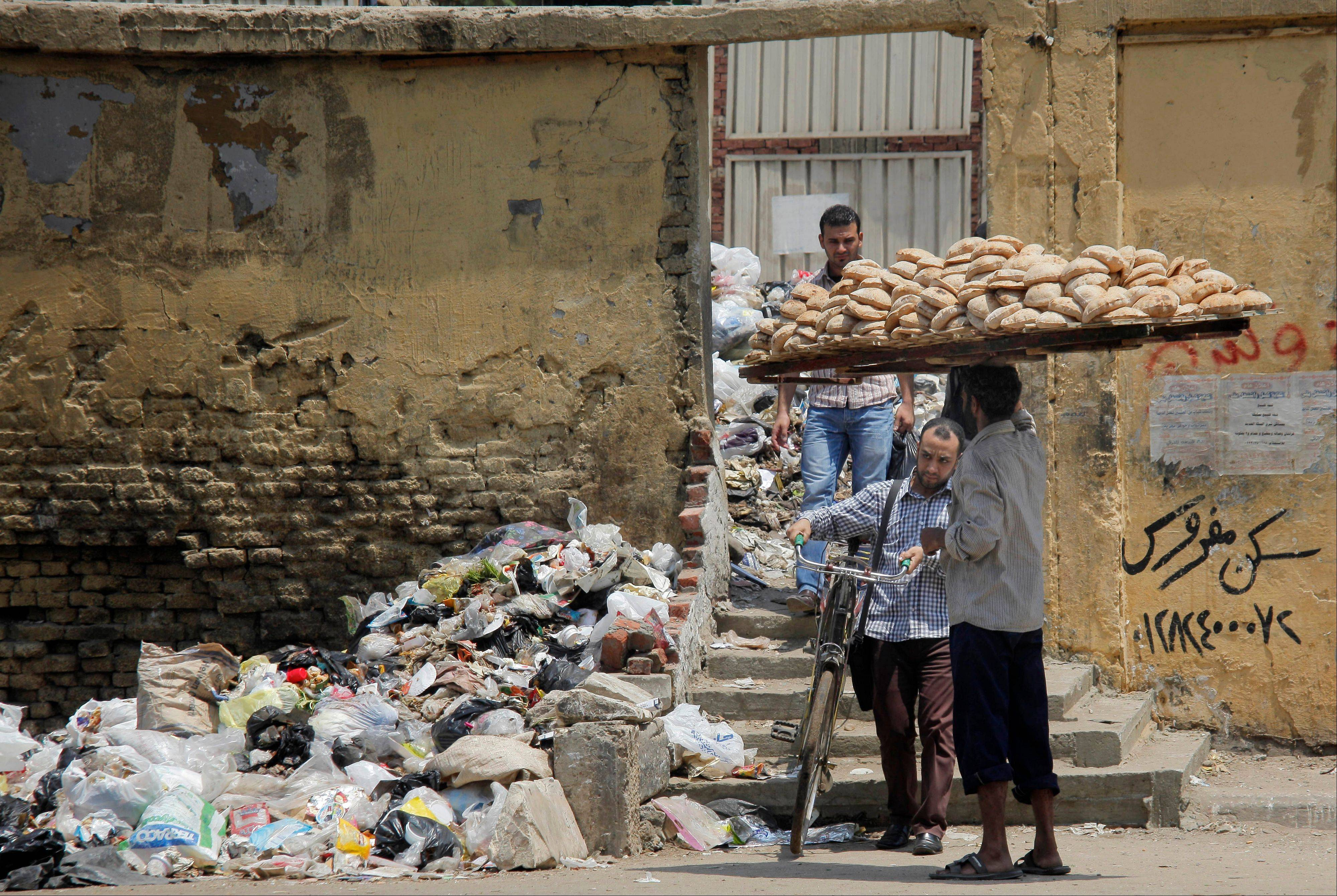 A bread vendor and others walk in front of loads of garbage on a Cairo street.
