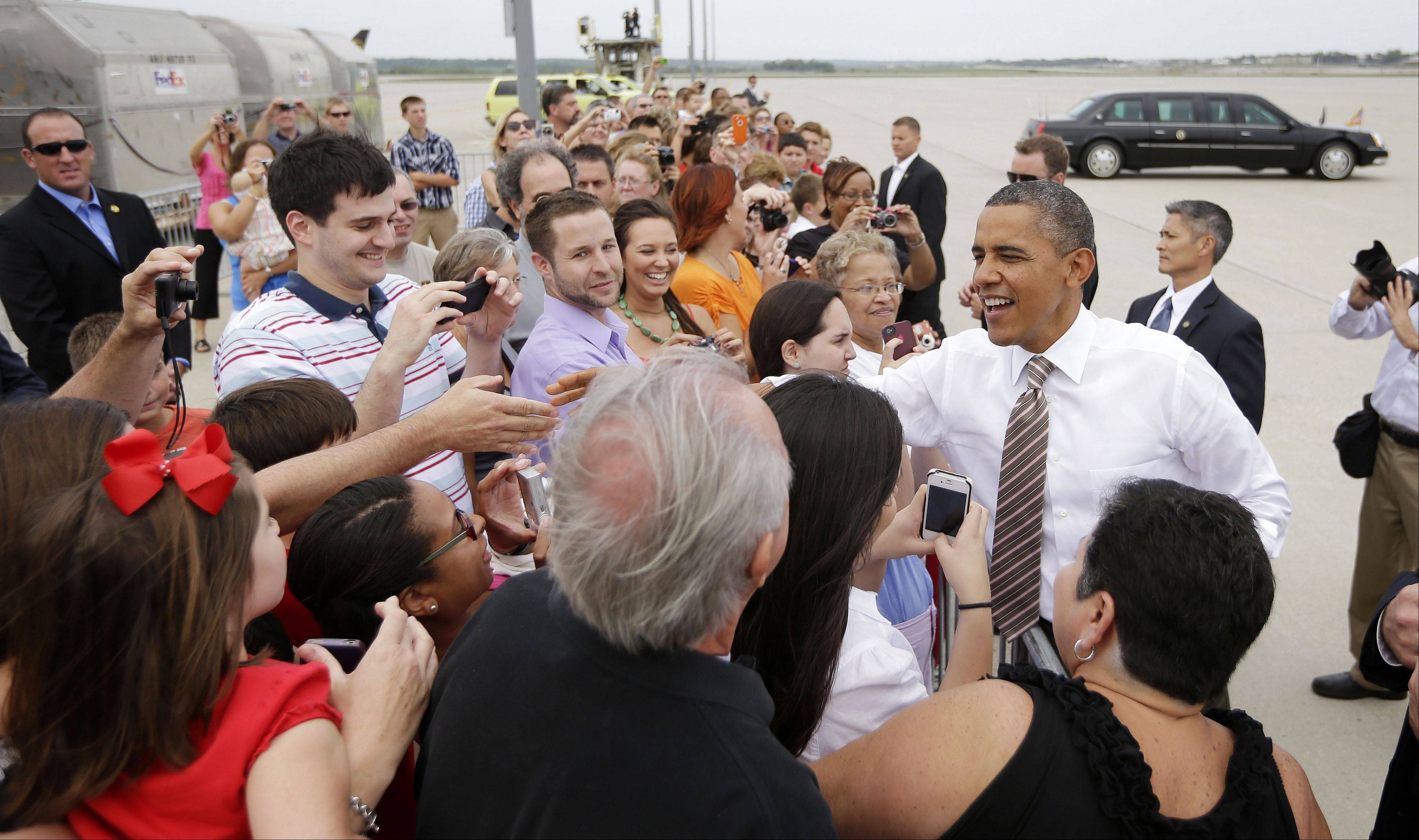 President Barack Obama greets guests on the tarmac upon his arrival at Des Moines International Airport, Saturday.