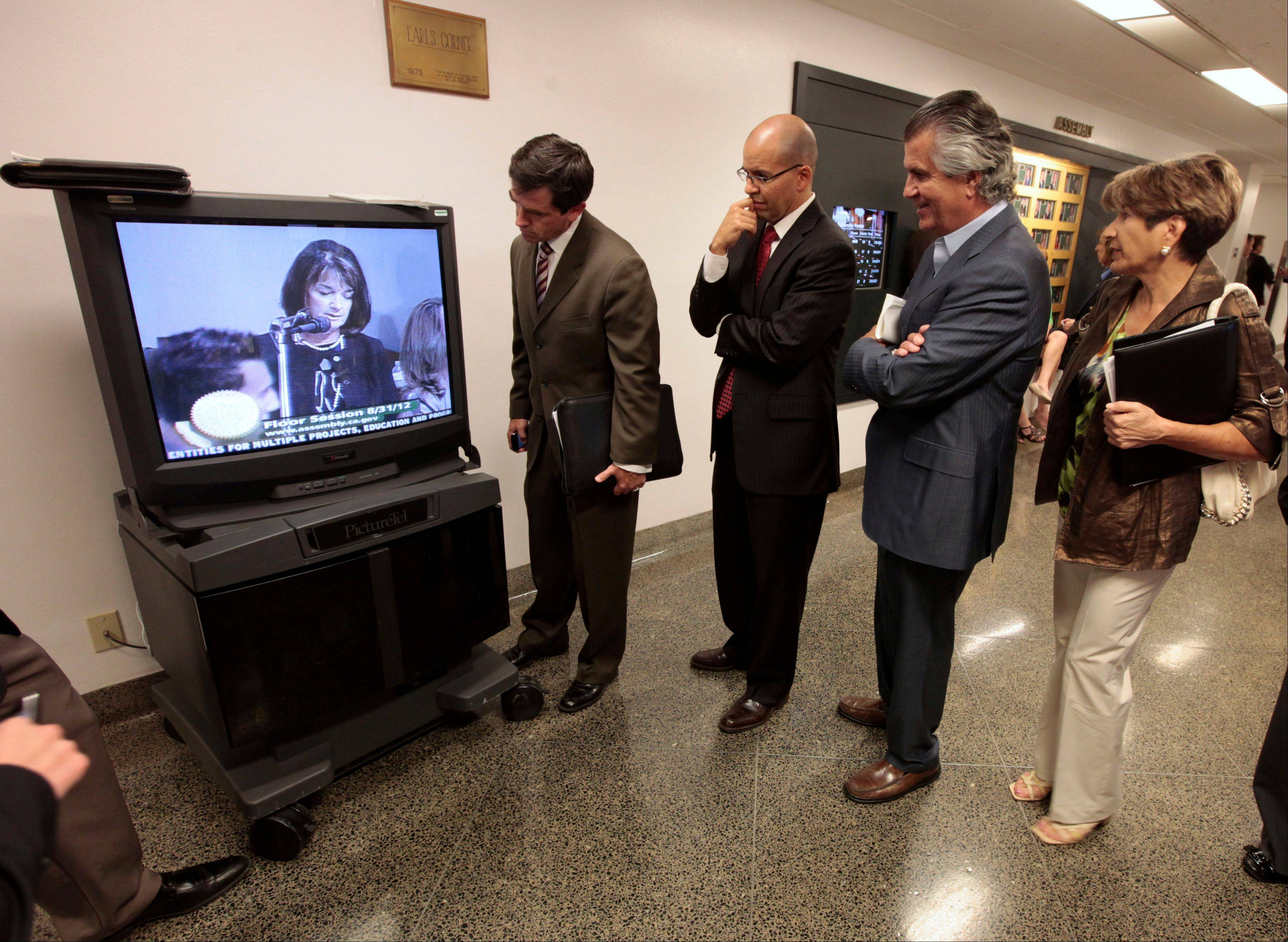 Lobbyist gather around a television monitor in the halls of the Capitol to watch the action in the Assembly during the final day of the Legislative session Friday in Sacramento, Calif.