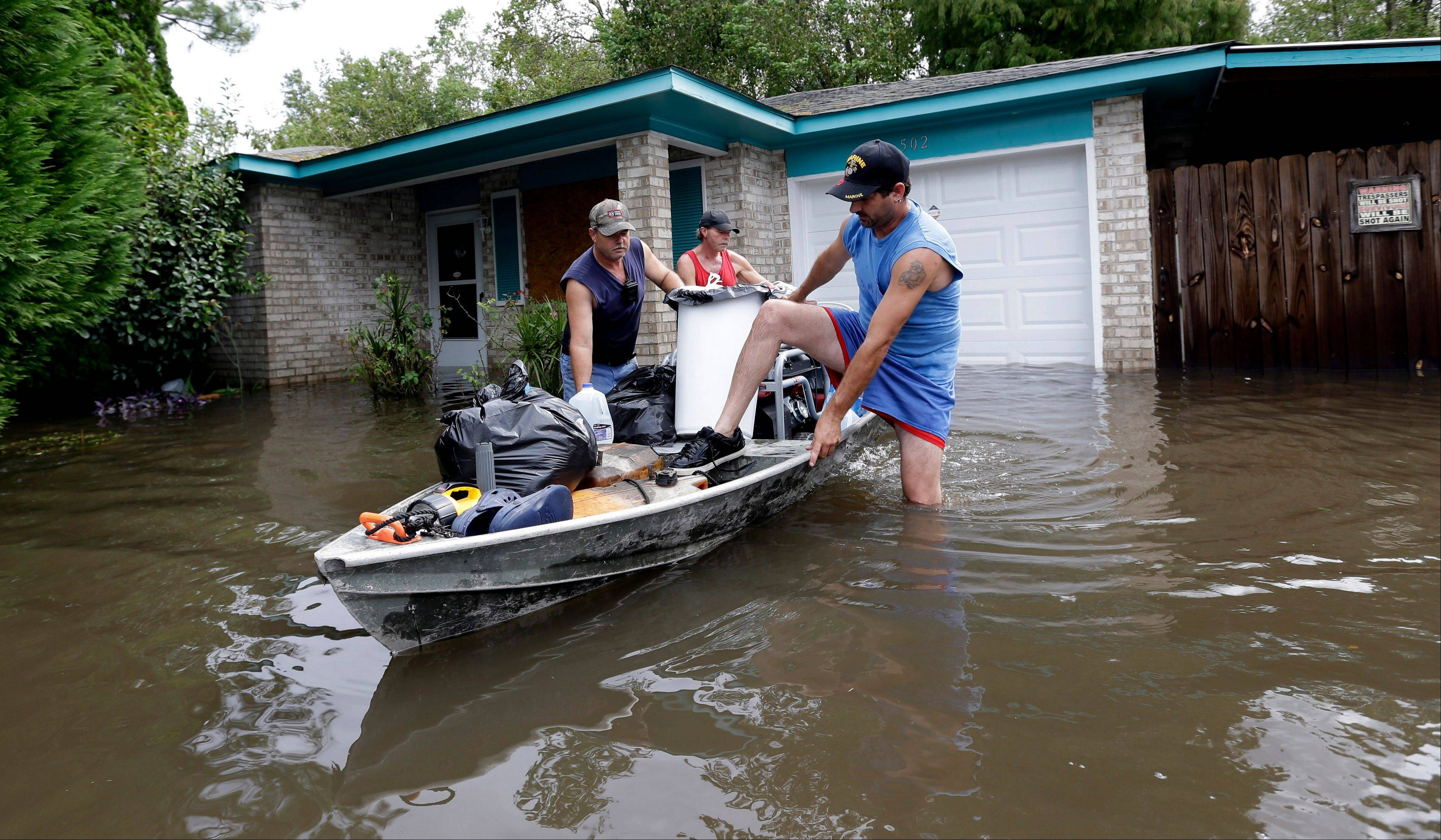 Christopher Tabb, left, uses a boat Friday to recover items from his flooded home in Reserve, La. Isaac crawled into the central U.S. on Friday evening, bringing with it torrential downpours and, today, tornado warnings and watches.