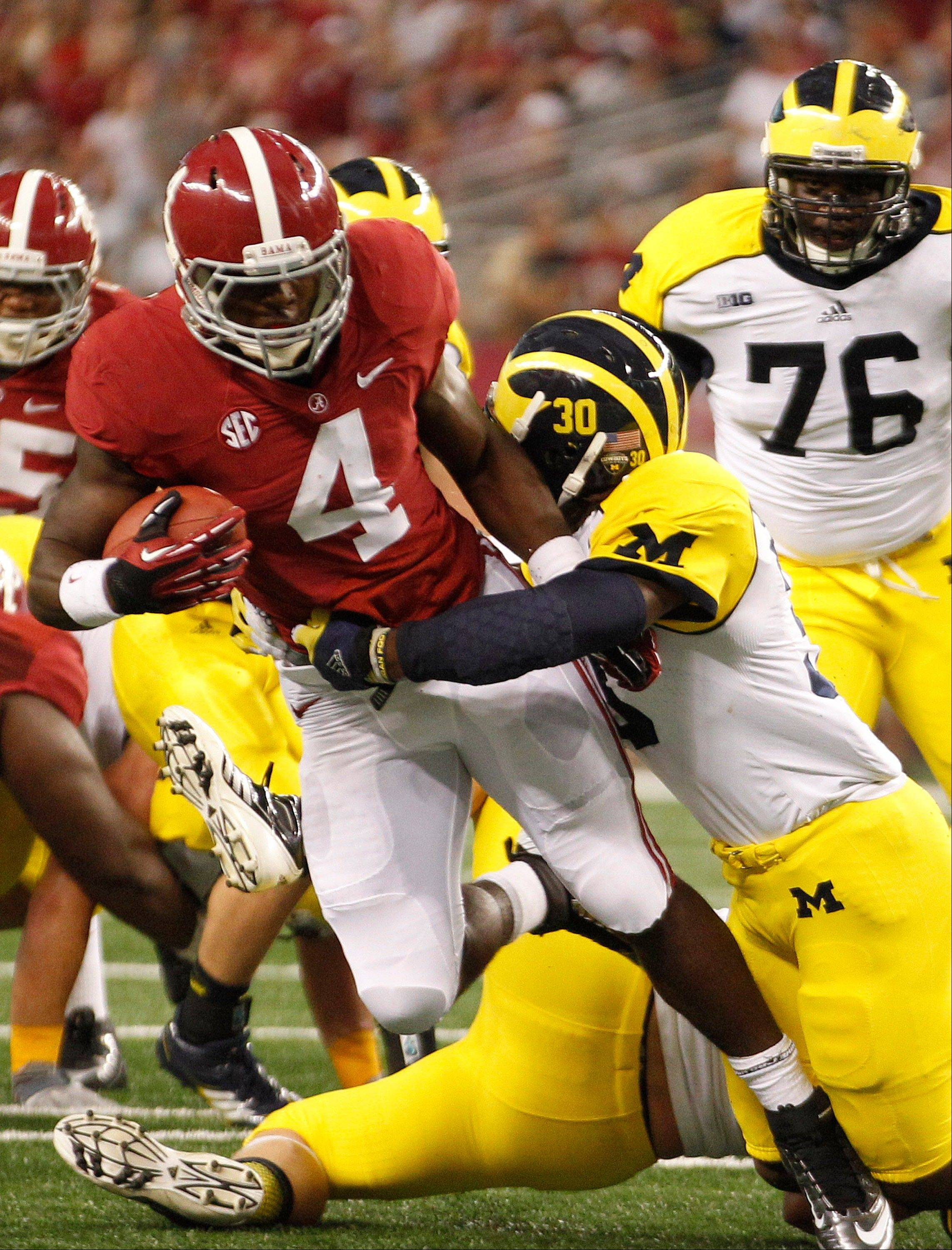 Alabama running back T.J. Yeldon (4) picks up yardage against Michigan safety Thomas Gordon (30) during the first half of an NCAA college football game Saturday at Cowboys Stadium in Arlington, Texas