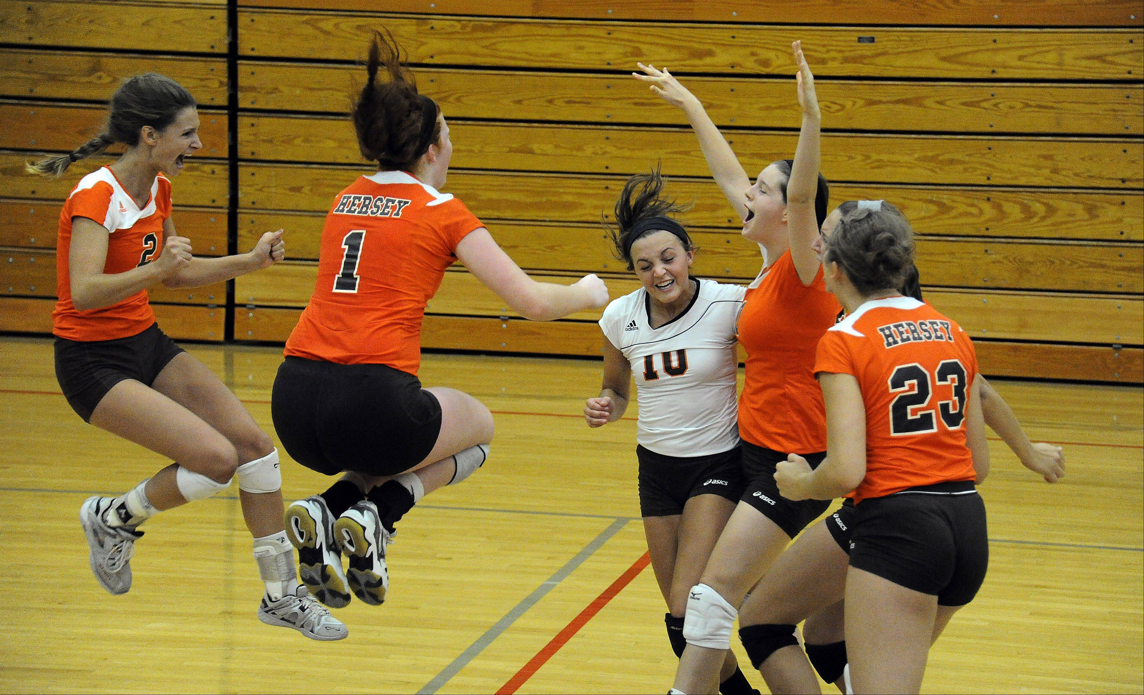 Hersey's Megan Solans, Abby Fesl and Taylor Hill celebrate the final point and the win in Game 3 against Waukesha Catholic Saturday at the Jacobs tournament.