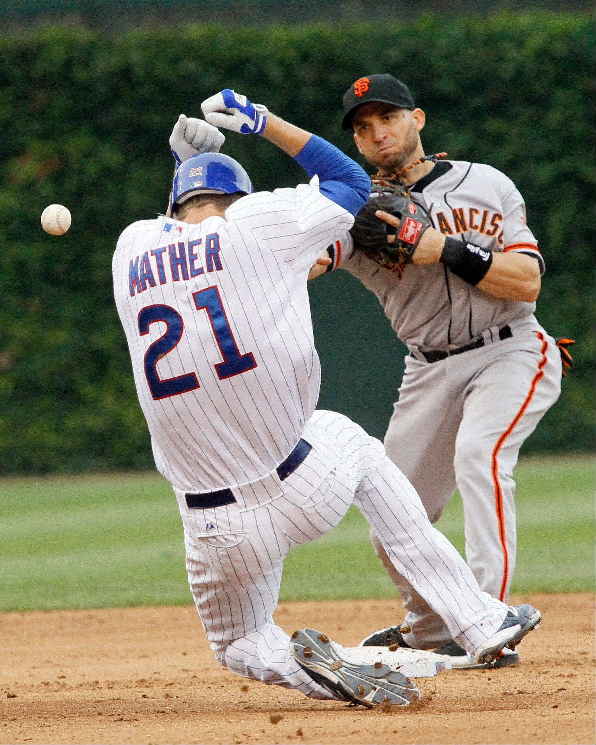 Chicago Cubs' Joe Mather ducks as San Francisco Giants second baseman Marco Scutaro turns the double play forcing Mather at second and getting Josh Vitters at first, during the eighth inning of a baseball game Saturday in Chicago.