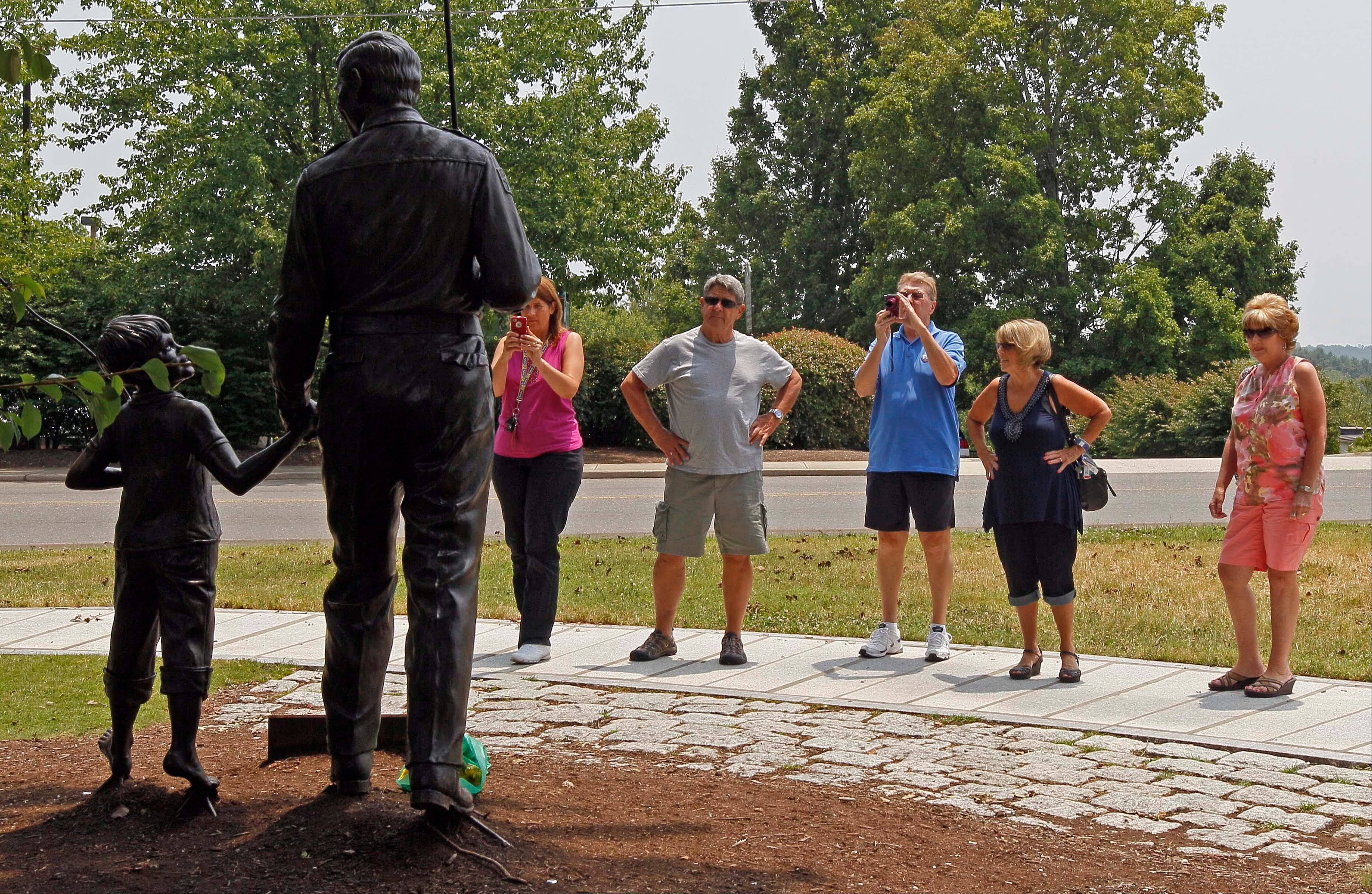 "People gather around a statue of Andy and Opie Taylor, characters from ""The Andy Griffith Show,"" at the Andy Griffith Playhouse in Mount Airy, N.C."