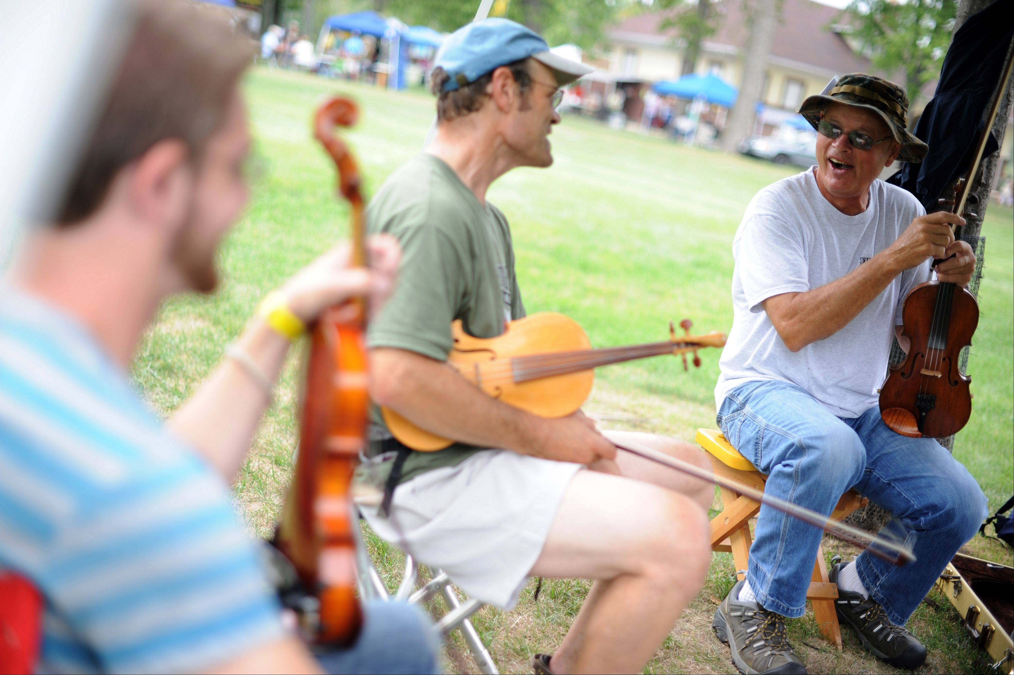Joe Samojedny, of Palatine, talks with fellow artists between jam sessions at the 36th Annual Fox Valley Folk Music and Storytelling Festival at Island Park in Geneva Sunday.