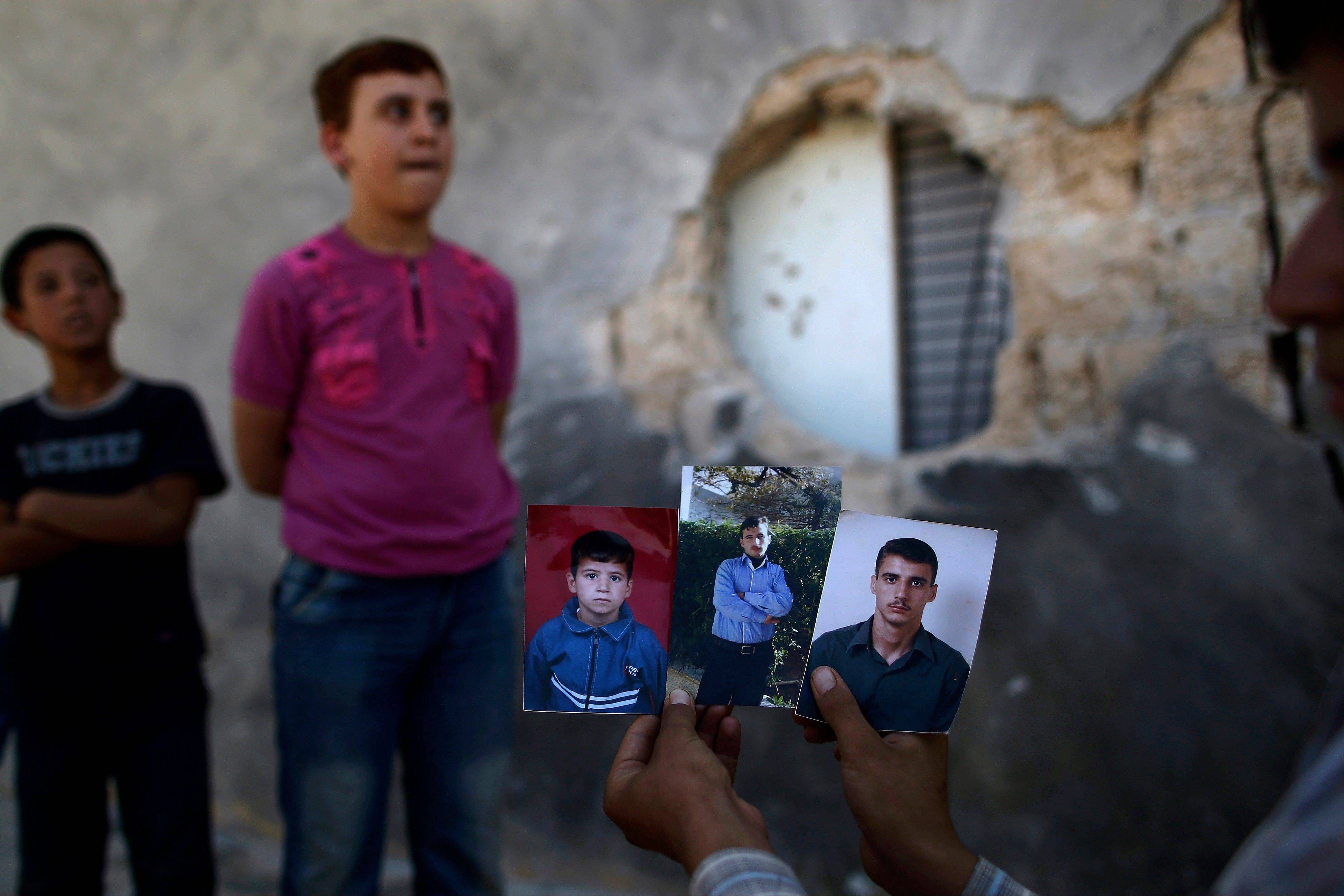 Syrian Hamzah Abu Bakri, displays portraits of his brothers who were killed Thursday by government shelling as they stood by their vegetable shop on the outskirts of Aleppo, Syria.